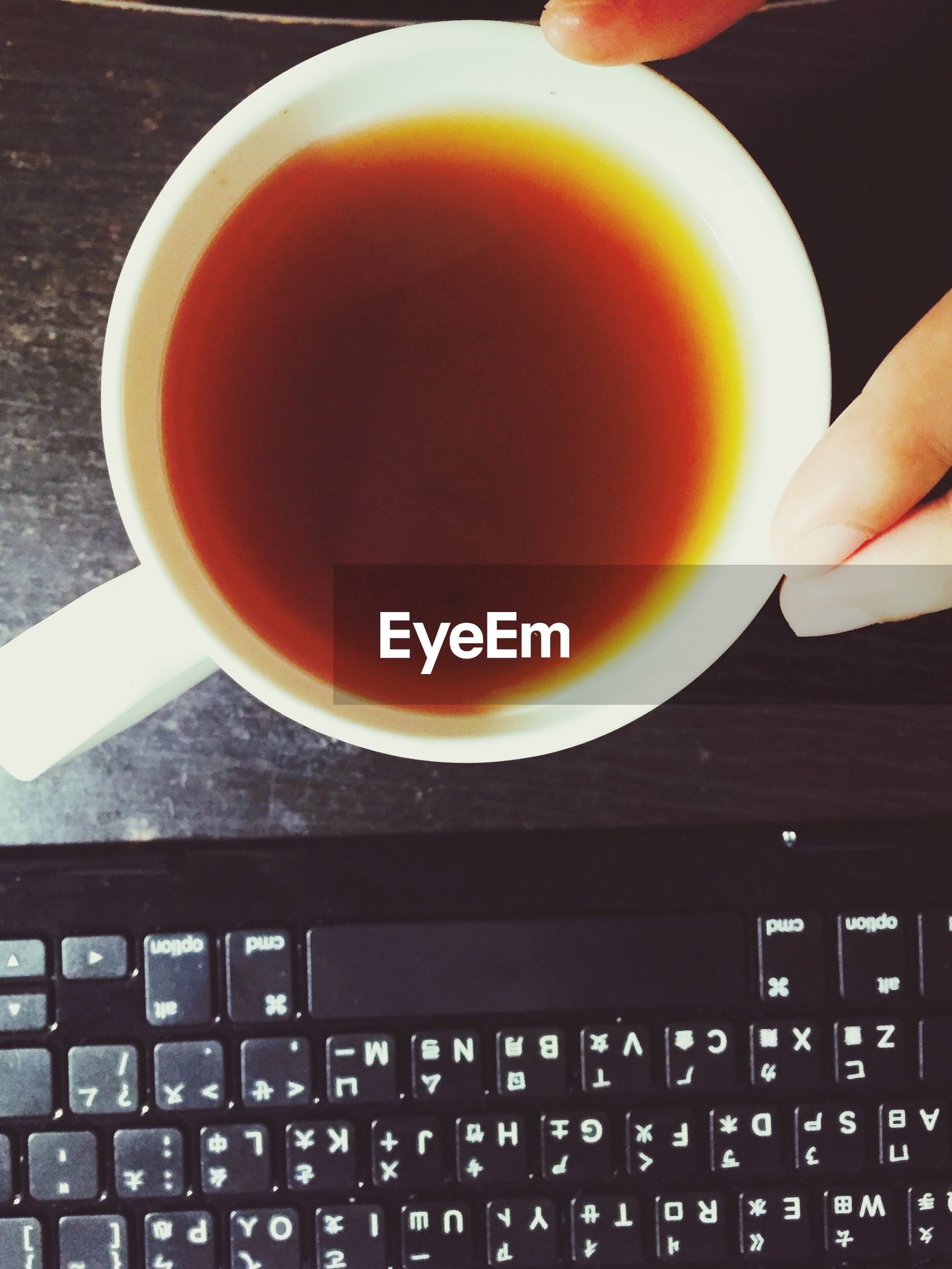 Cropped hands holding tea cup by computer keyboard