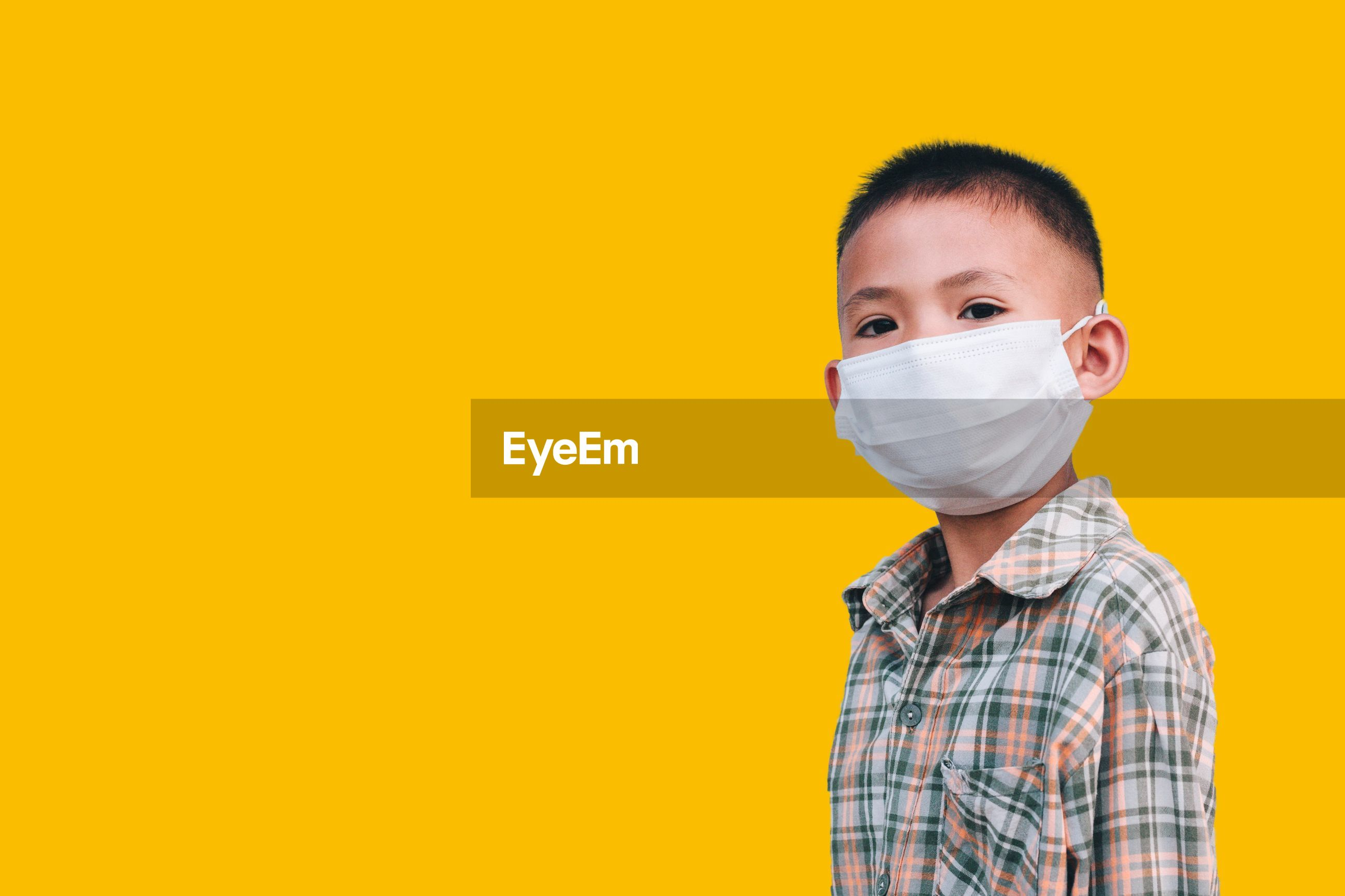 Portrait of boy wearing mask against yellow background