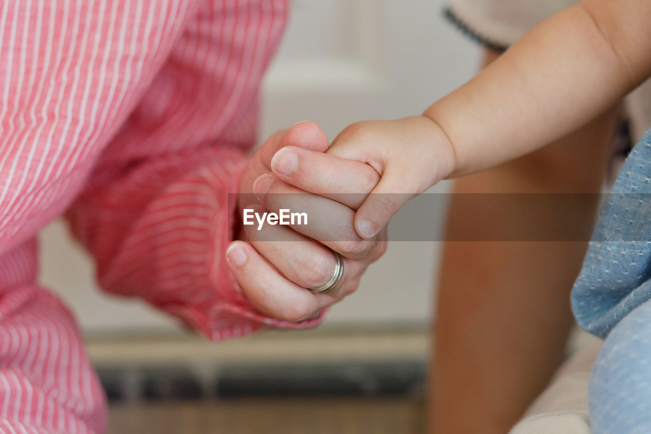 Close-Up Of Mother Holding Baby Hand At Home