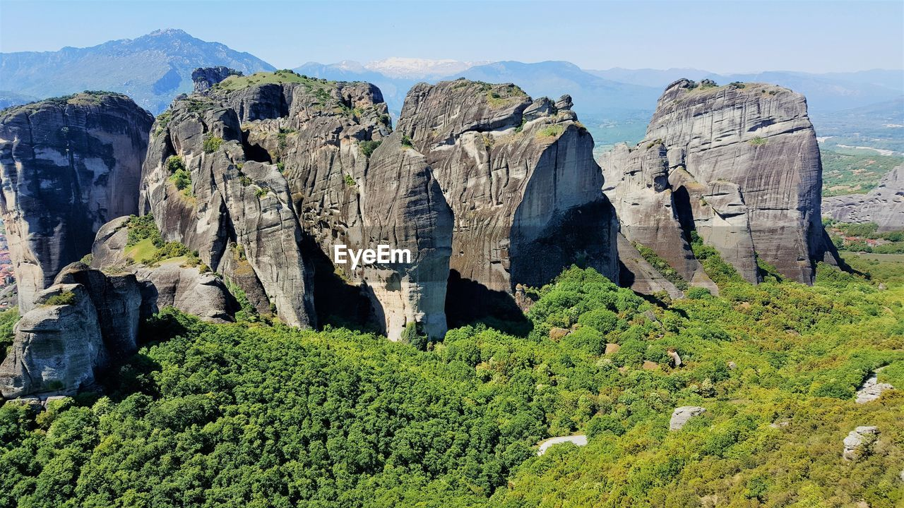 Panoramic view of meteora rocks on landscape against sky