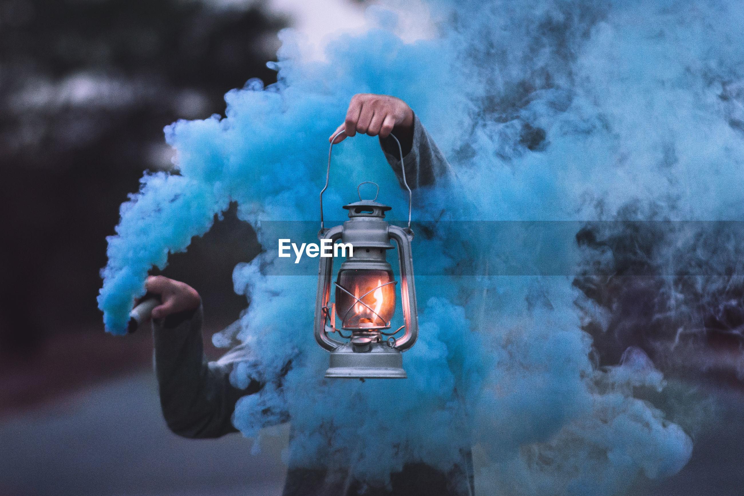 Person holding illuminated lantern amidst blue smoke