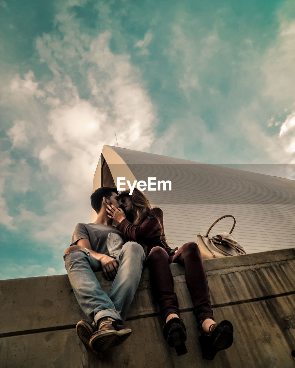 Low Angle View Of Couple Romancing Against Building In City