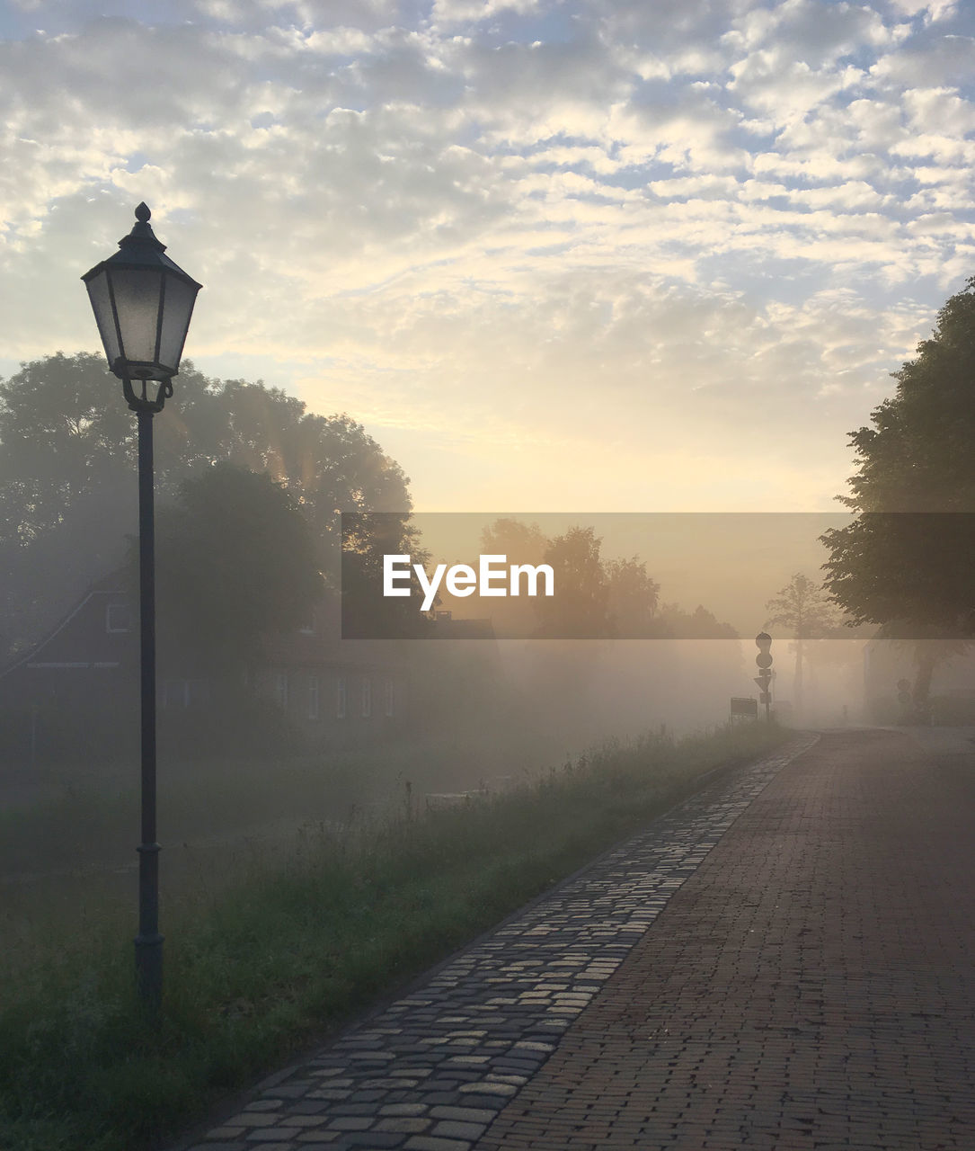 STREET LIGHT BY FOOTPATH AGAINST SKY