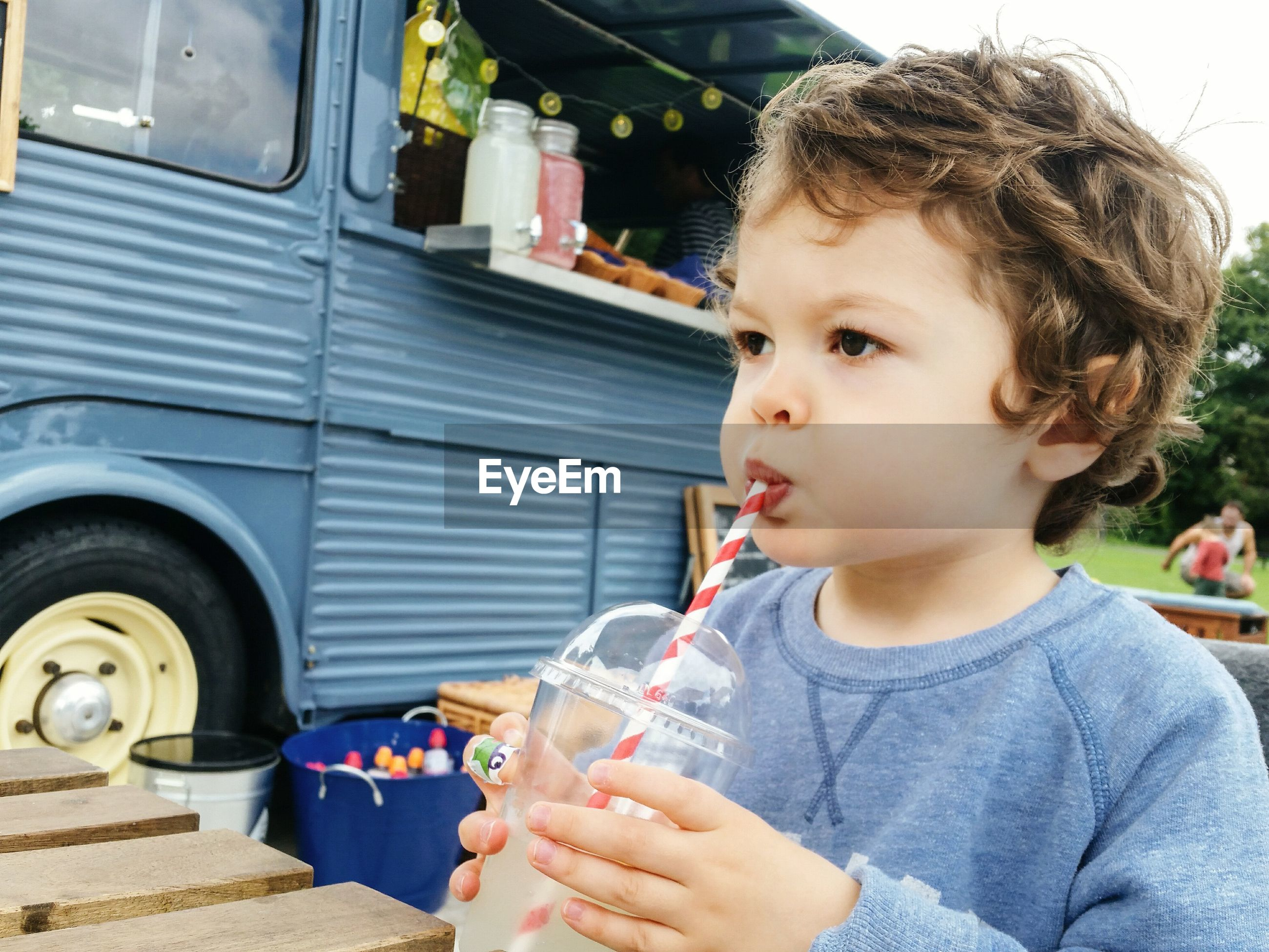 Close-up of cute boy drinking lemonade while looking away outdoors