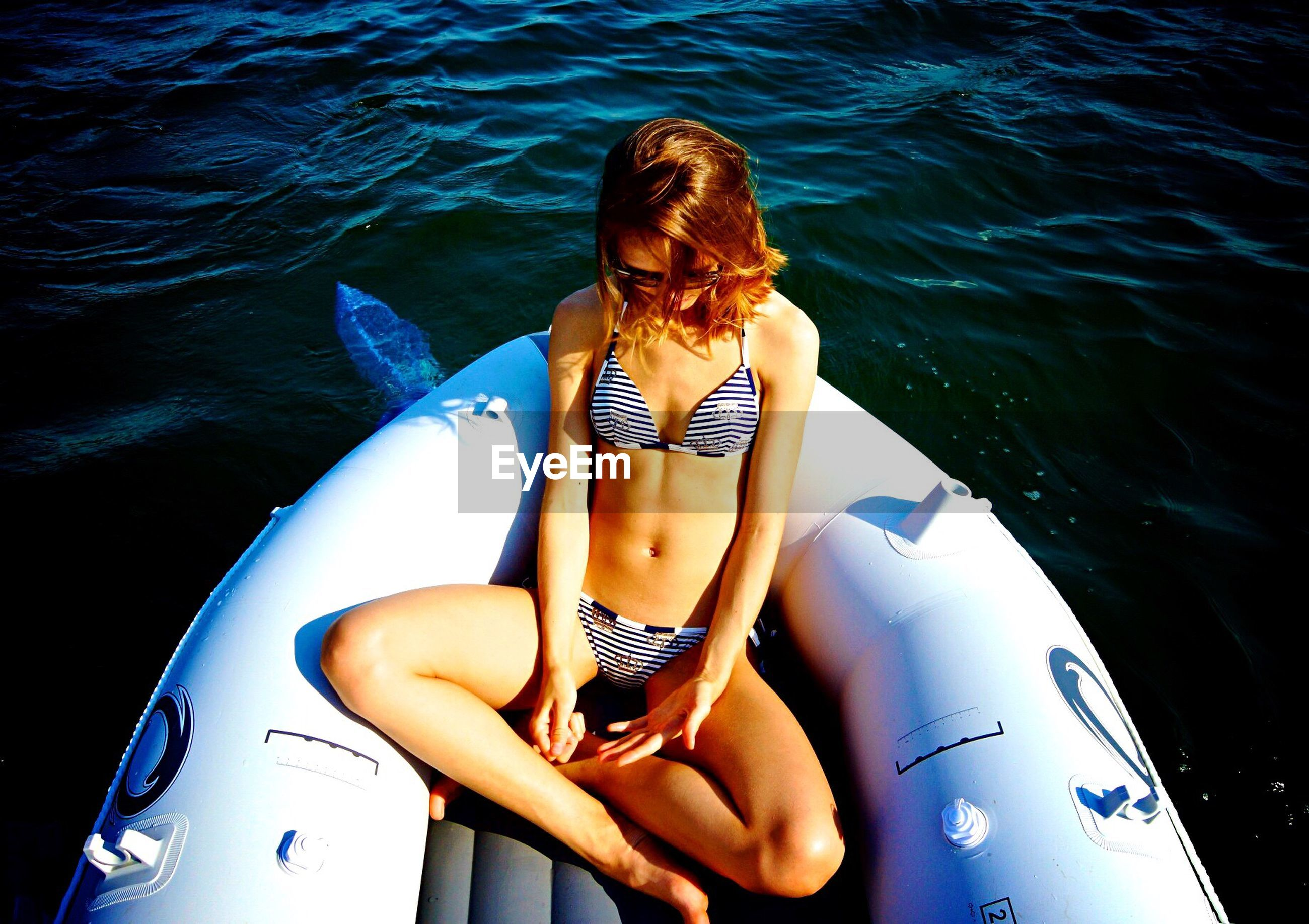 High angle view of young woman relaxing on raft