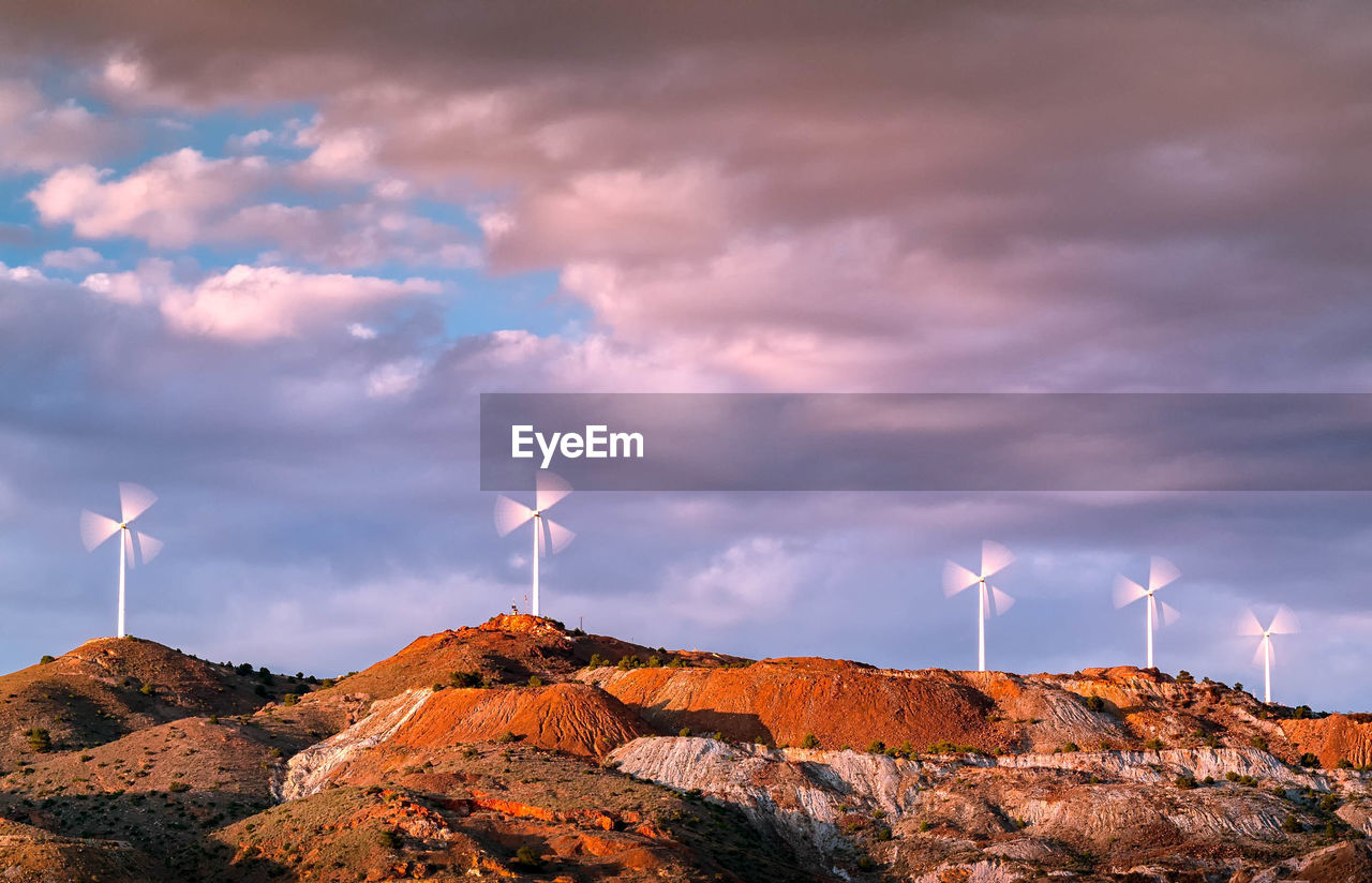 Wind Turbines On Mountain Against Sky
