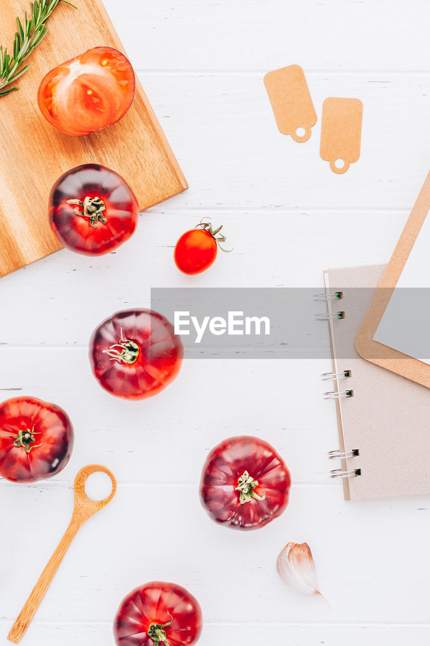 food, food and drink, healthy eating, still life, fruit, high angle view, indoors, freshness, table, wellbeing, vegetable, directly above, wood - material, tomato, no people, cutting board, red, medium group of objects, white color, close-up