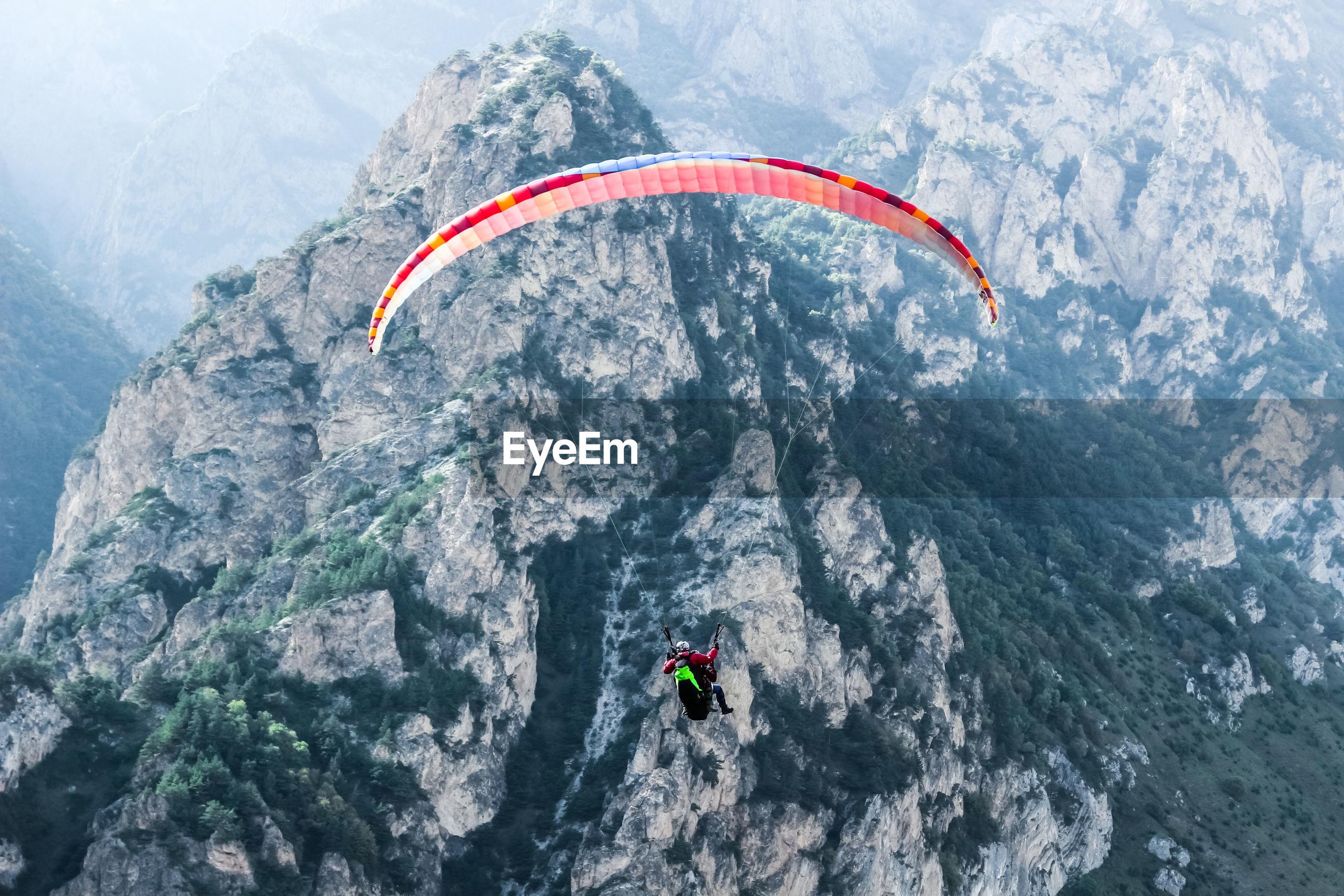 People paragliding on mountain peak