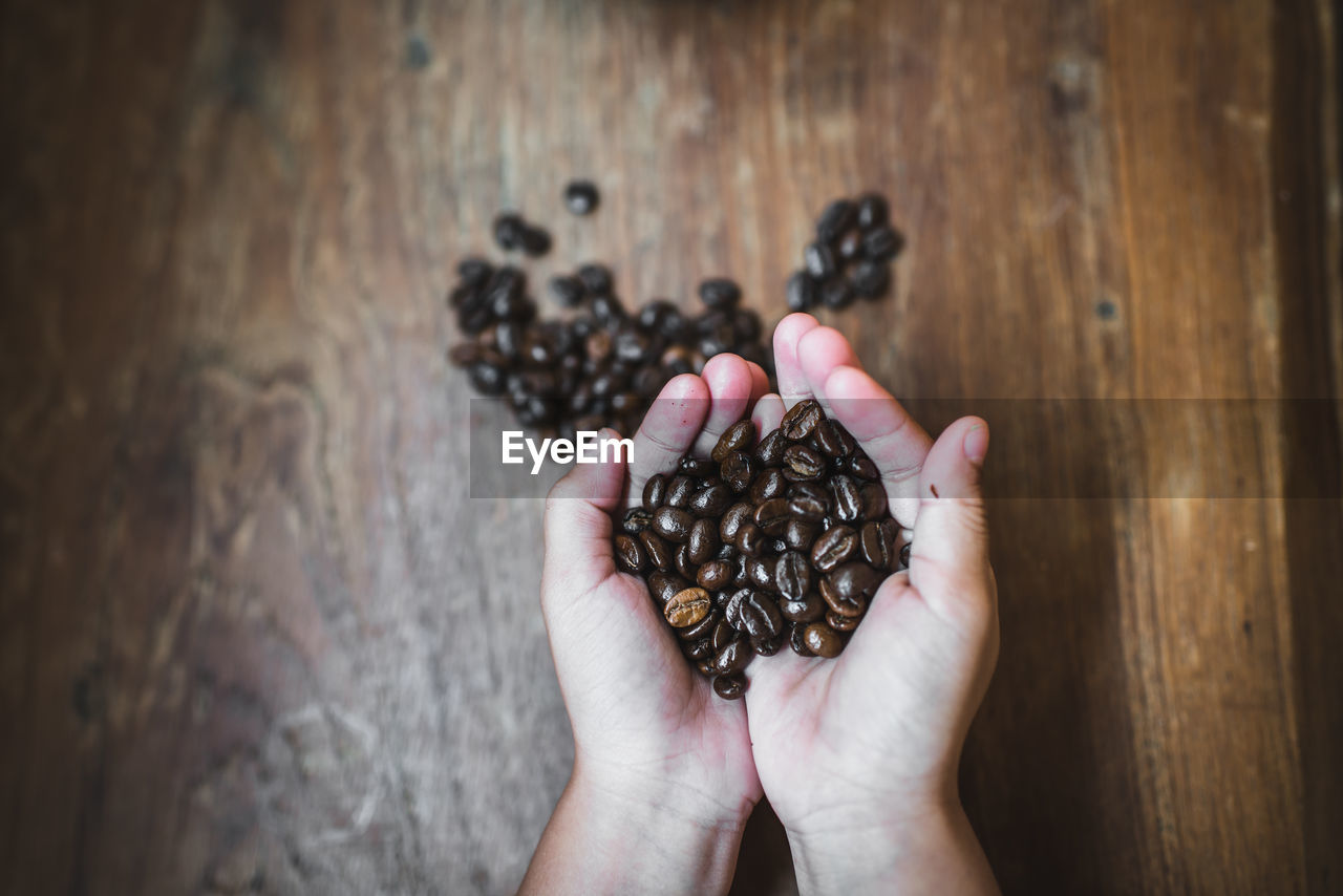 hand, human hand, food and drink, real people, food, holding, human body part, one person, unrecognizable person, freshness, indoors, hands cupped, high angle view, close-up, coffee, coffee - drink, lifestyles, brown, table, body part, finger