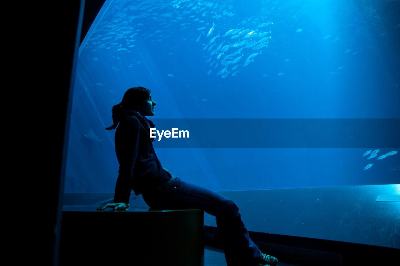 Woman sitting in aquarium