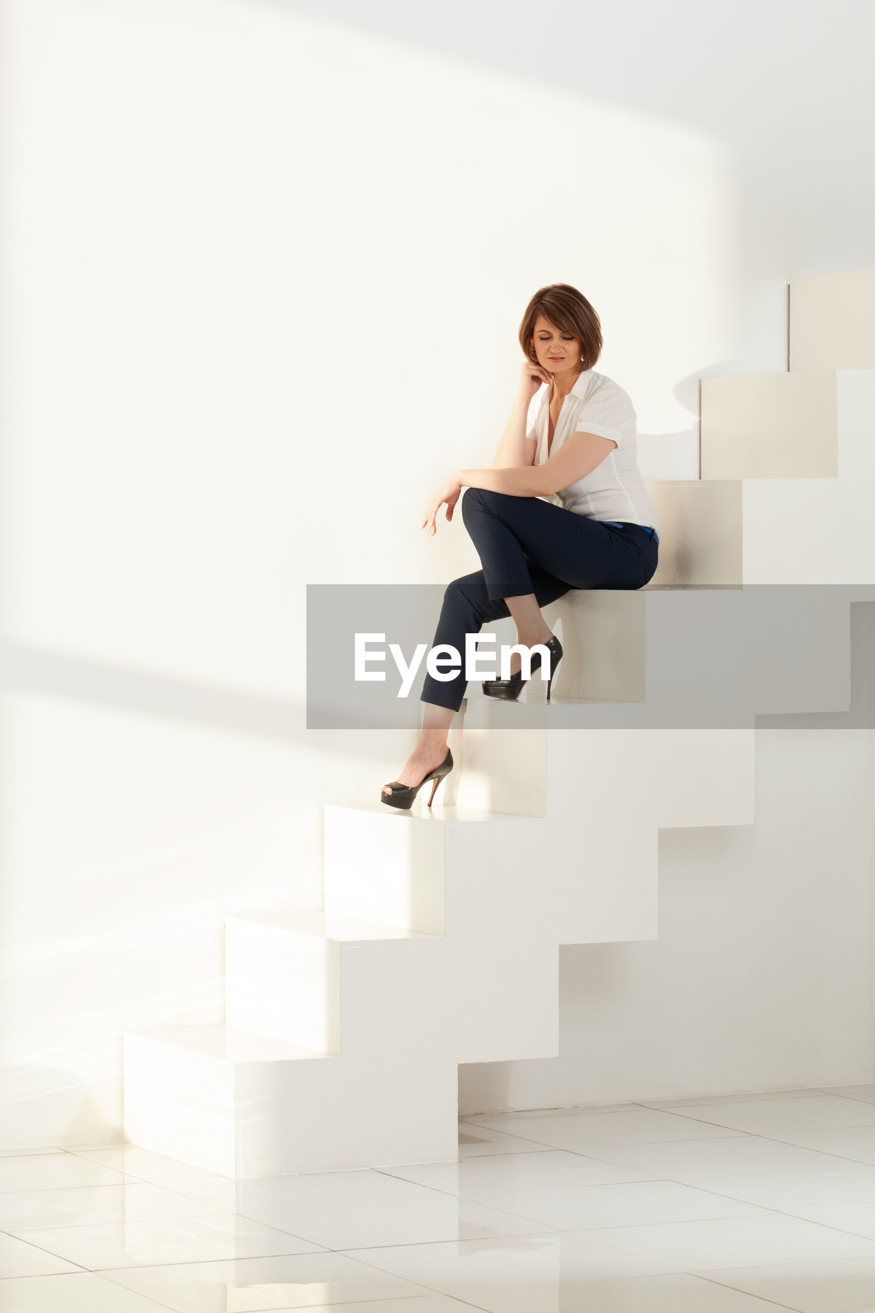 Businesswoman looking down while sitting on steps in office