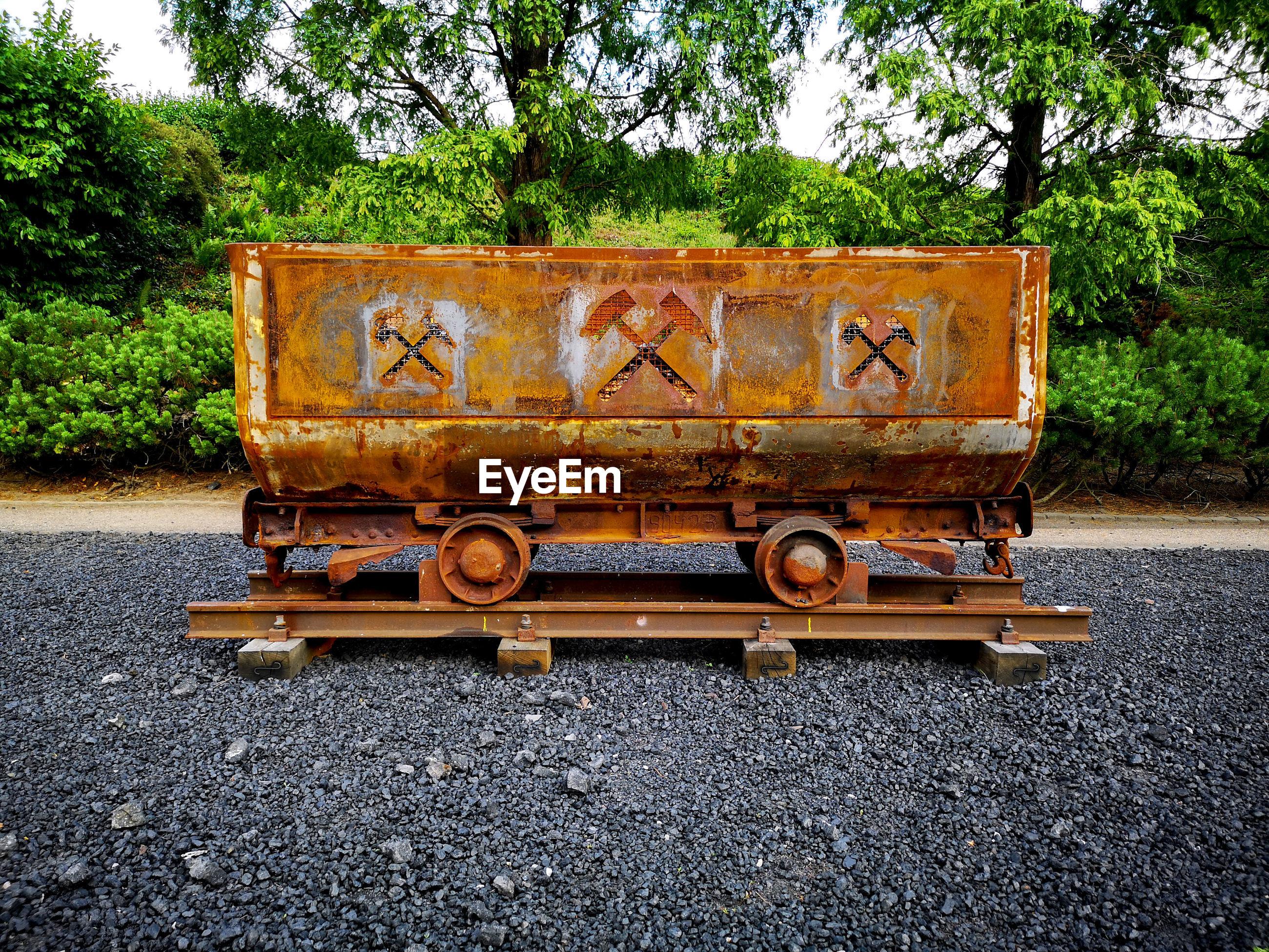Abandoned train on railroad track against trees