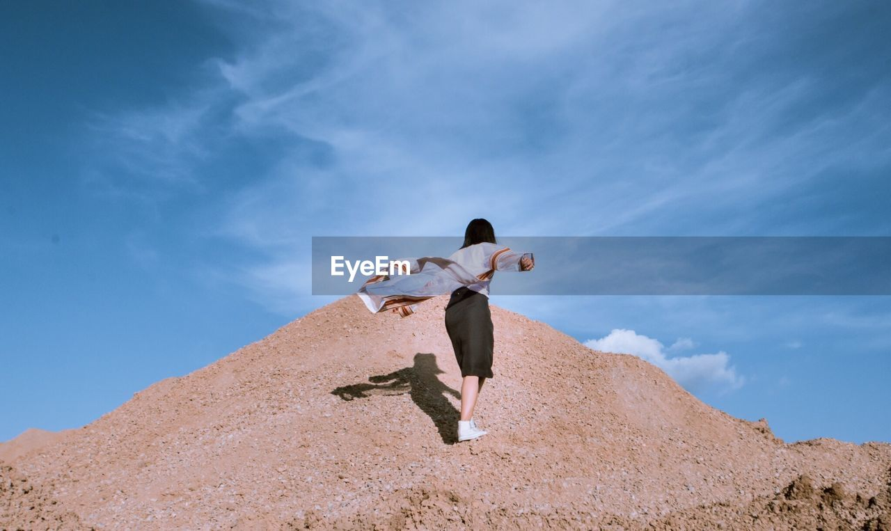 Low angle view of woman standing on mountain against sky