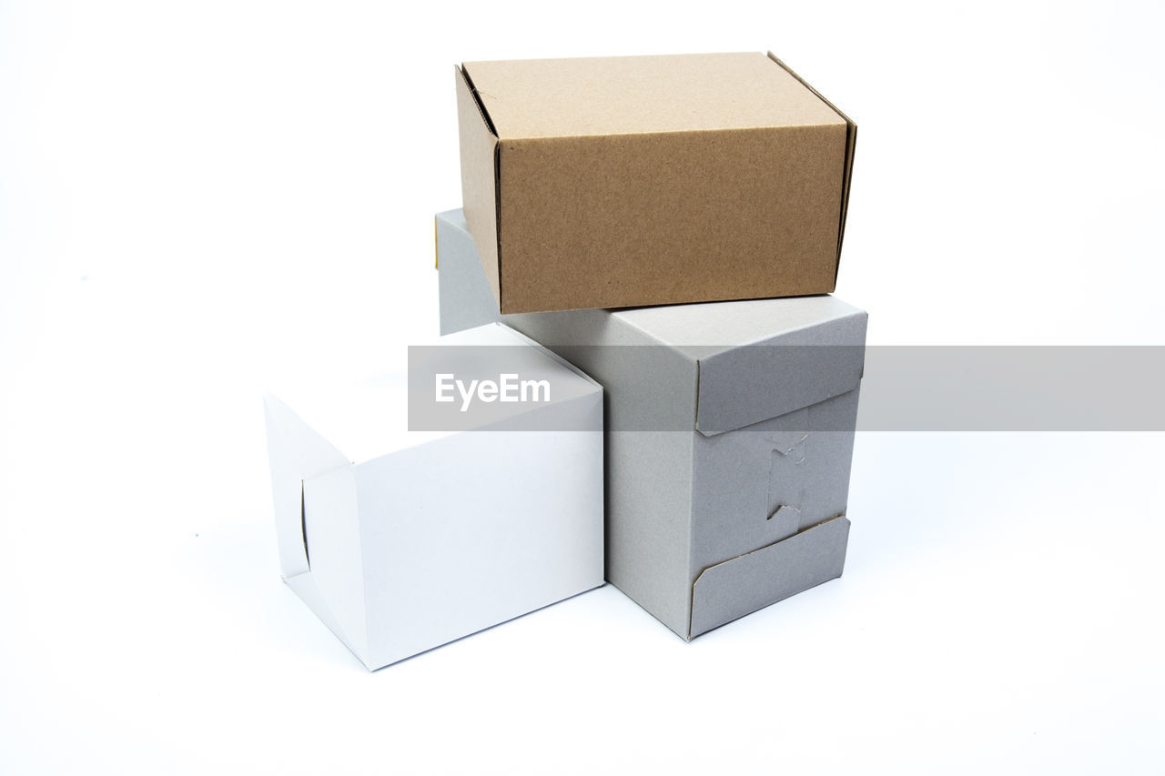 white background, studio shot, box, cardboard, still life, indoors, paper, box - container, no people, container, cut out, cardboard box, copy space, stack, close-up, cube shape, white color, group of objects, package, toy, blank