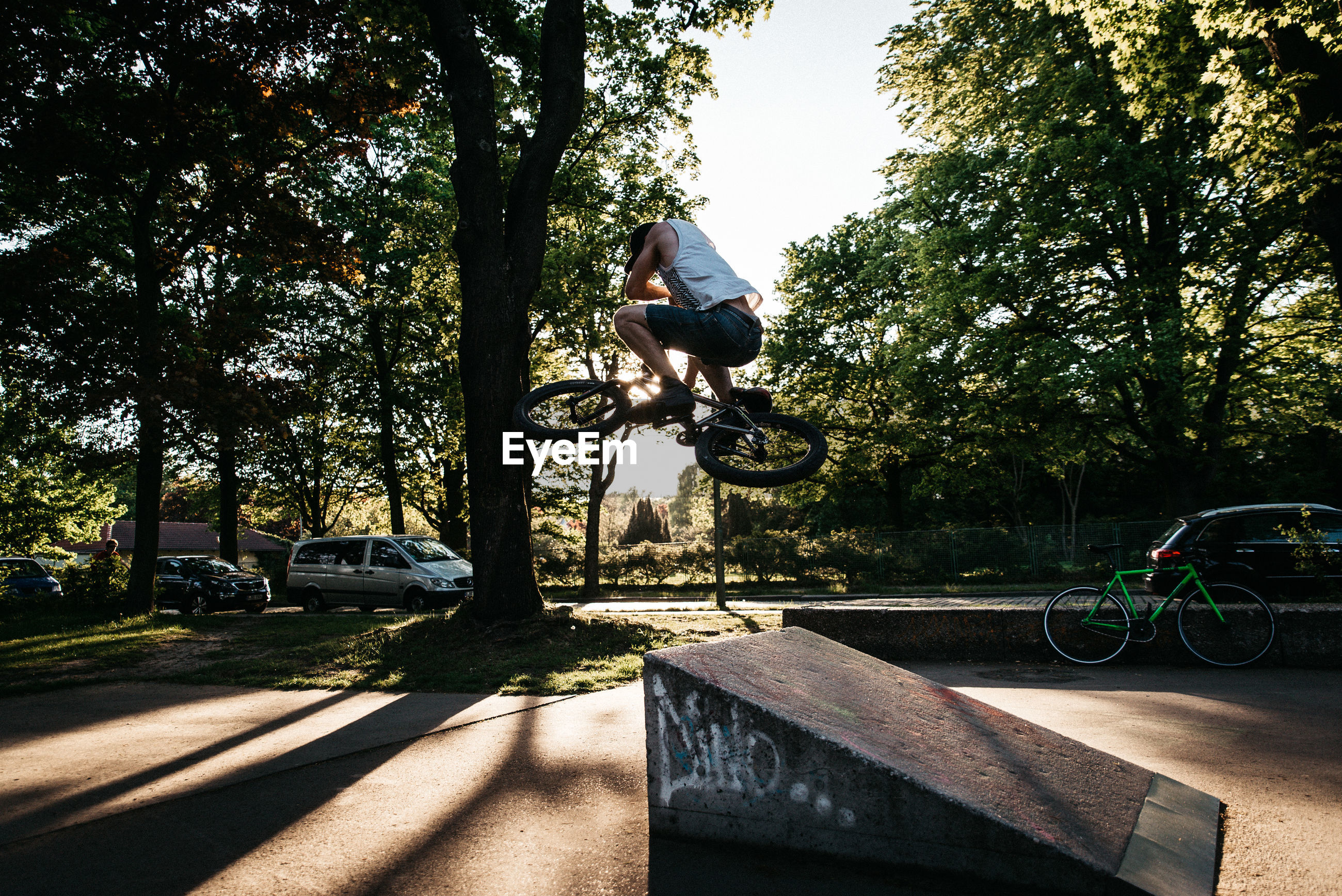 Man doing stunts with bicycle against trees