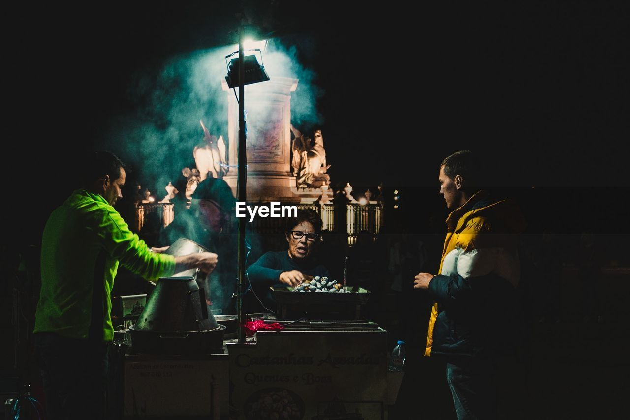 PEOPLE STANDING BY ILLUMINATED STREET LIGHT AT NIGHT