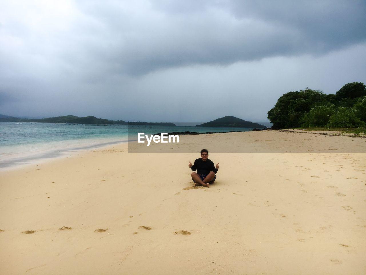 Man sitting on sand against cloudy sky at beach
