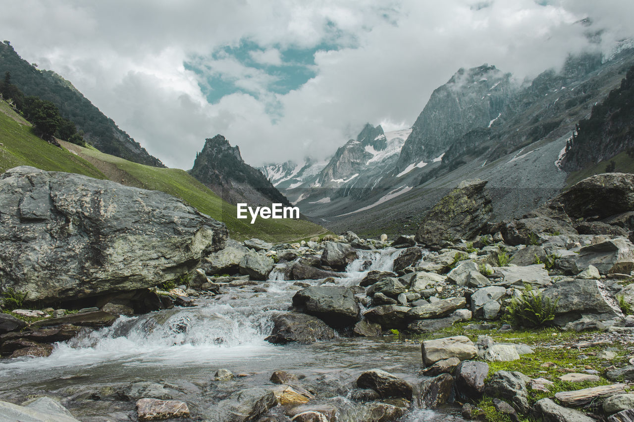 mountain, water, beauty in nature, environment, sky, nature, landscape, scenics - nature, rock, day, cloud - sky, scenery, solid, no people, rock - object, flowing water, outdoors, river, mountain range, flowing, mountain peak