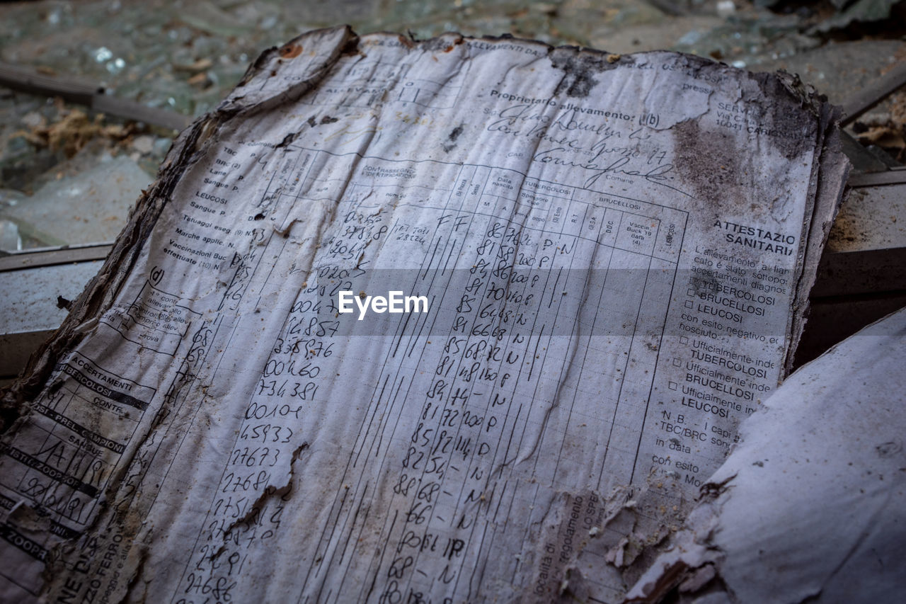 no people, high angle view, old, history, text, close-up, the past, paper, wood - material, communication, indoors, architecture, day, damaged, still life, tombstone, selective focus, single object, nature