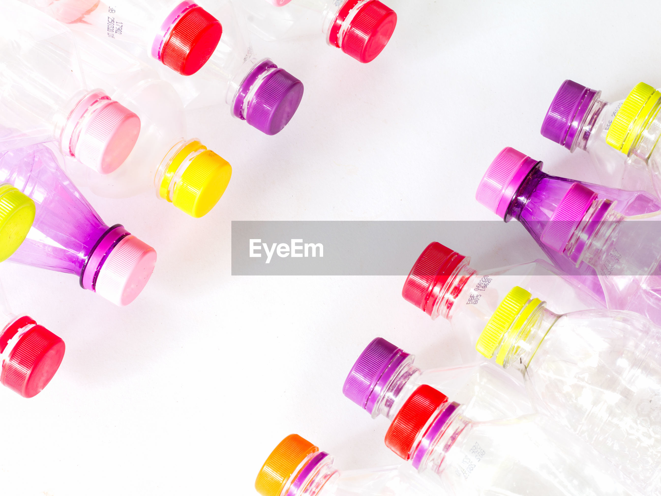 High angle view of multi colored bottles and caps against white background