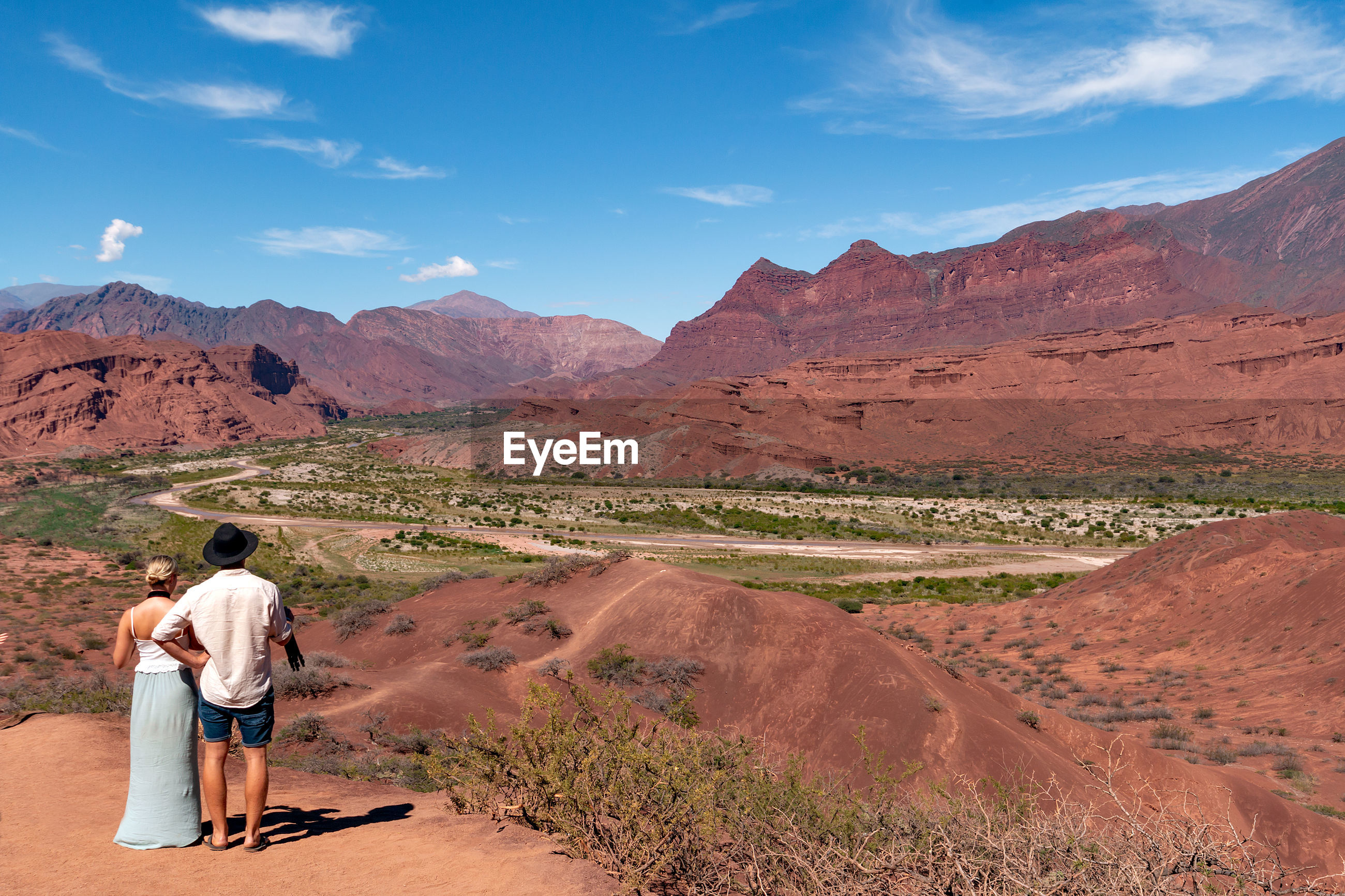 REAR VIEW OF MAN STANDING ON MOUNTAIN ROAD AGAINST SKY