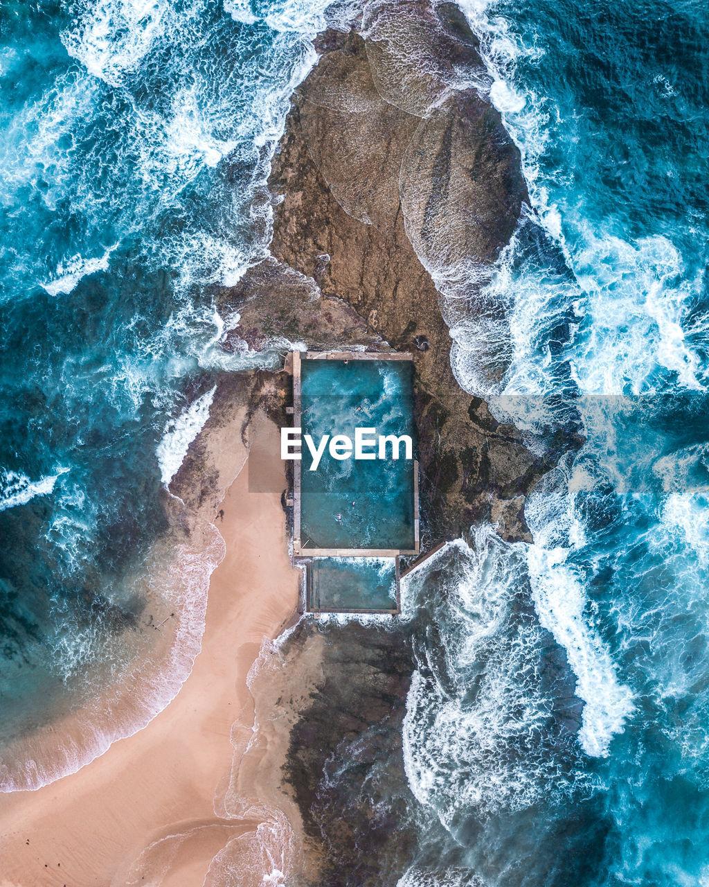 Aerial view of waves splashing on rocks at beach