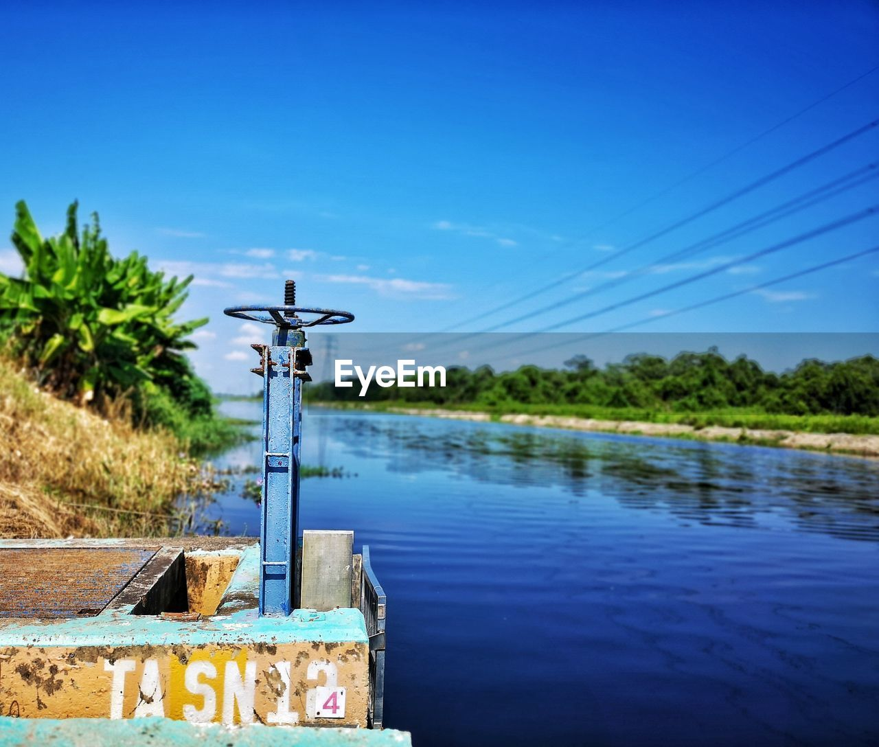 water, sky, nature, blue, plant, no people, day, tree, metal, outdoors, lake, growth, clear sky, land, focus on foreground, beauty in nature, field, tranquility, sunlight