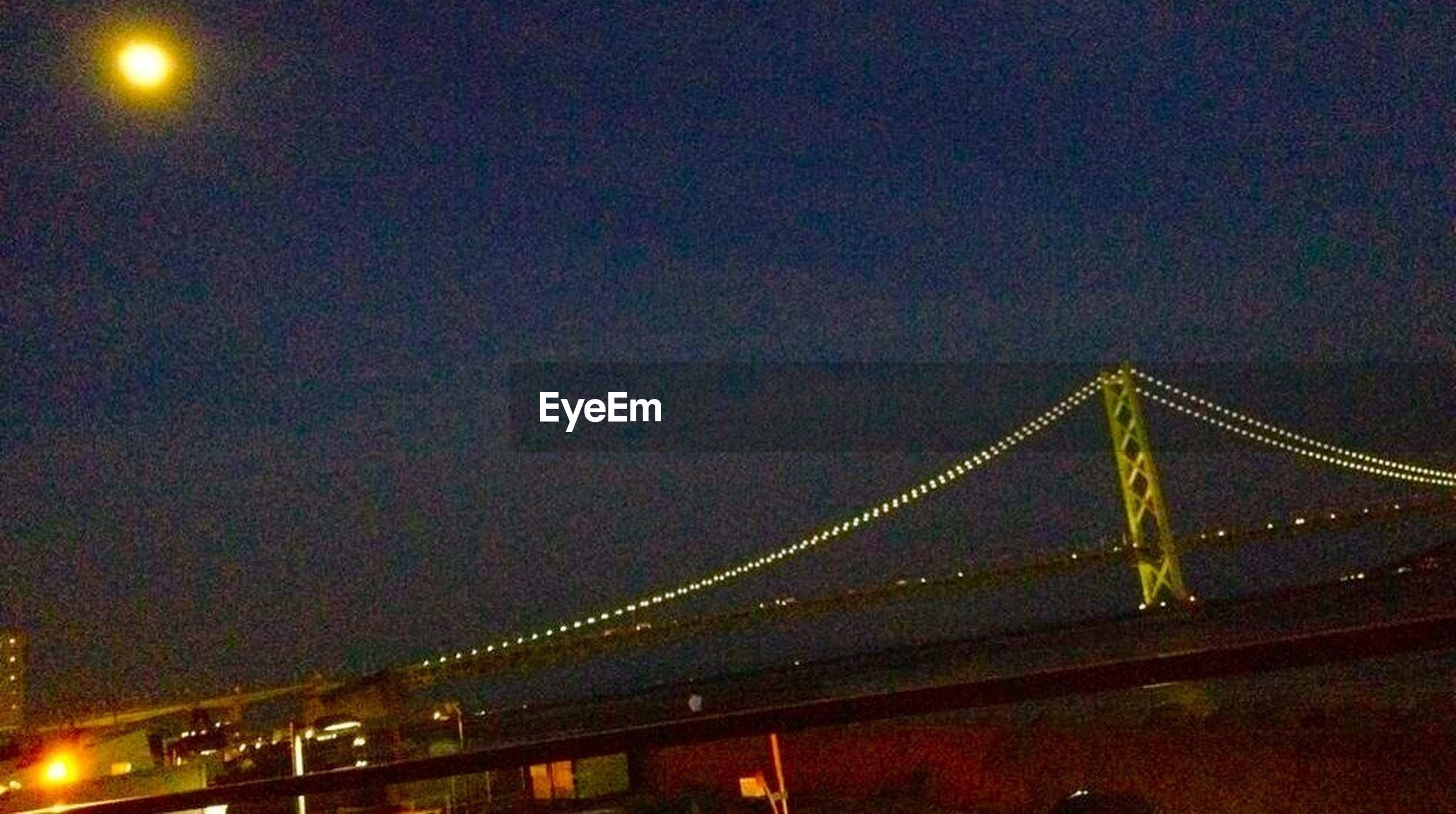 night, illuminated, architecture, built structure, low angle view, sky, moon, lighting equipment, connection, city, light - natural phenomenon, building exterior, light, bridge - man made structure, copy space, outdoors, dark, street light, glowing, no people