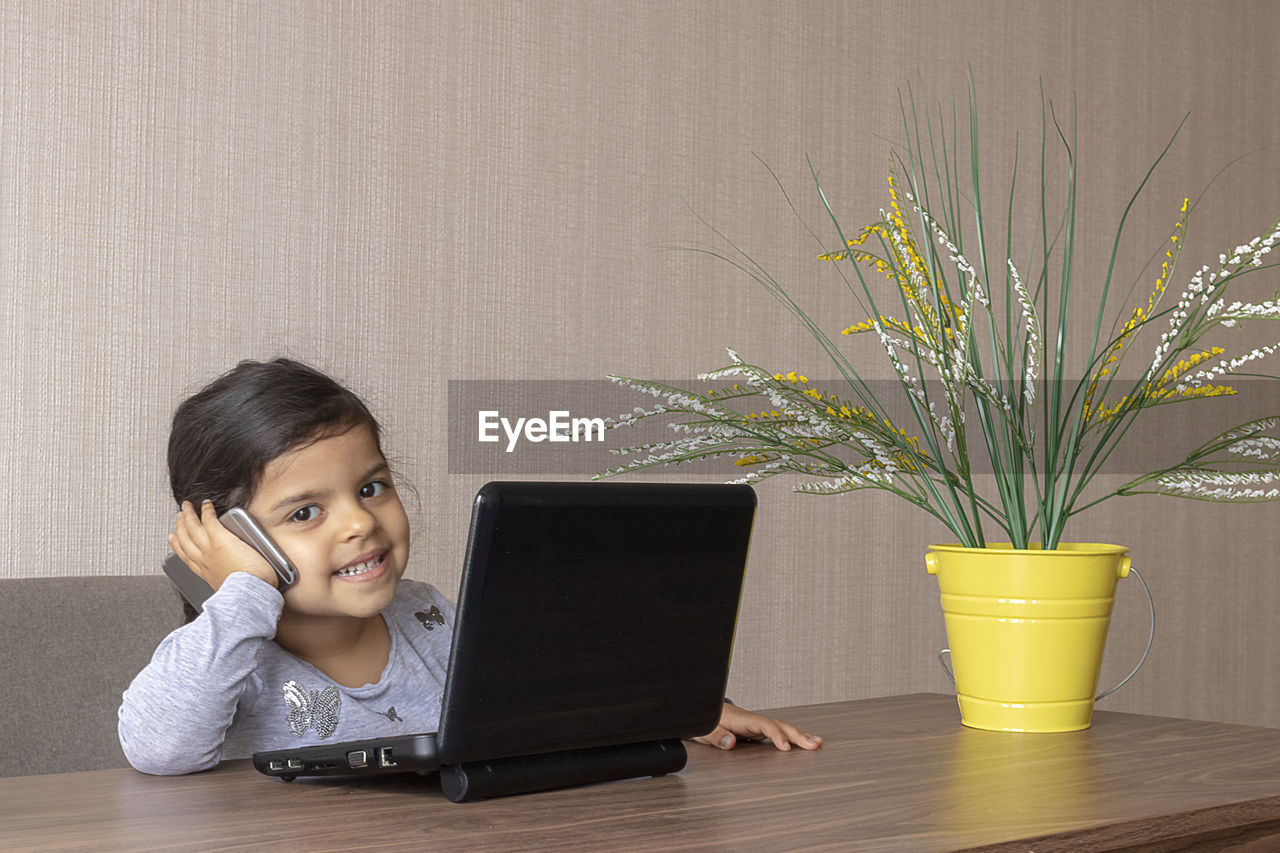 Portrait of girl using laptop while imitating at businesswoman