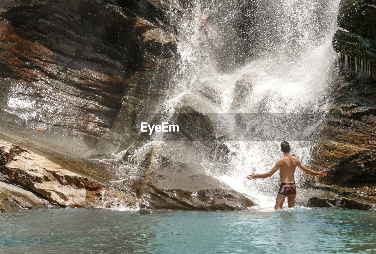 Rear view of shirtless man standing by waterfall