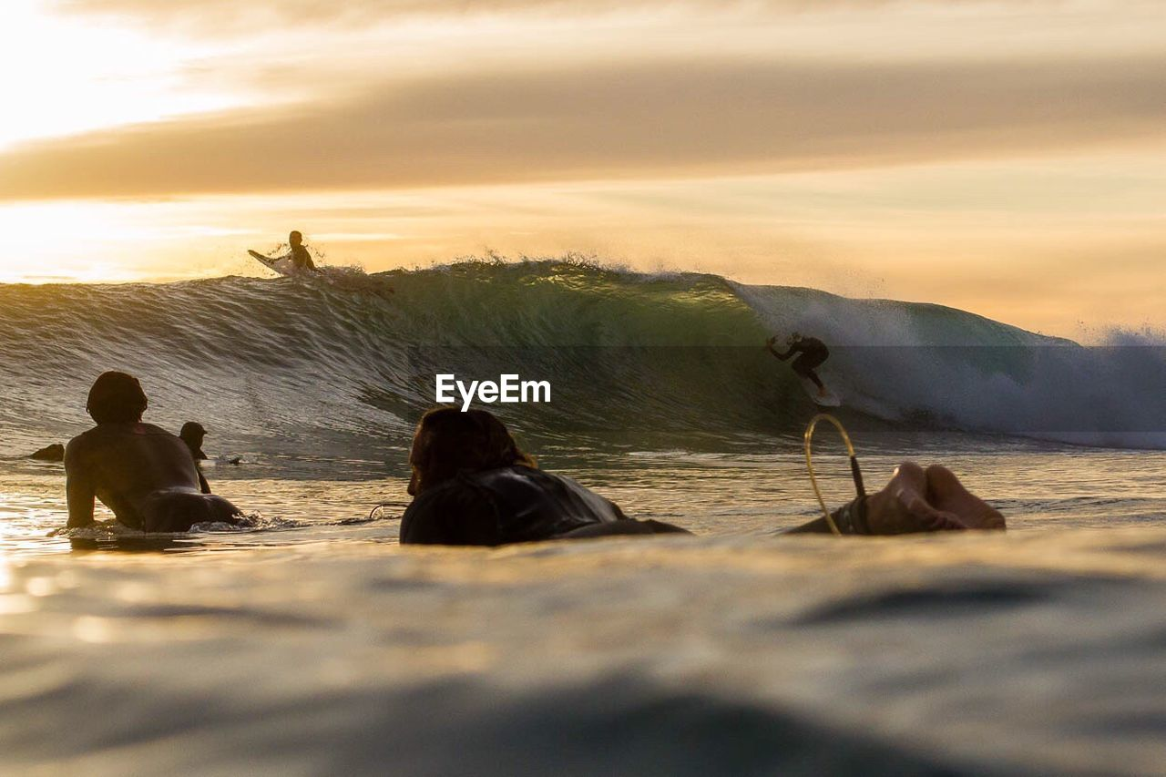 Scenic View Of Surfers During Sunset