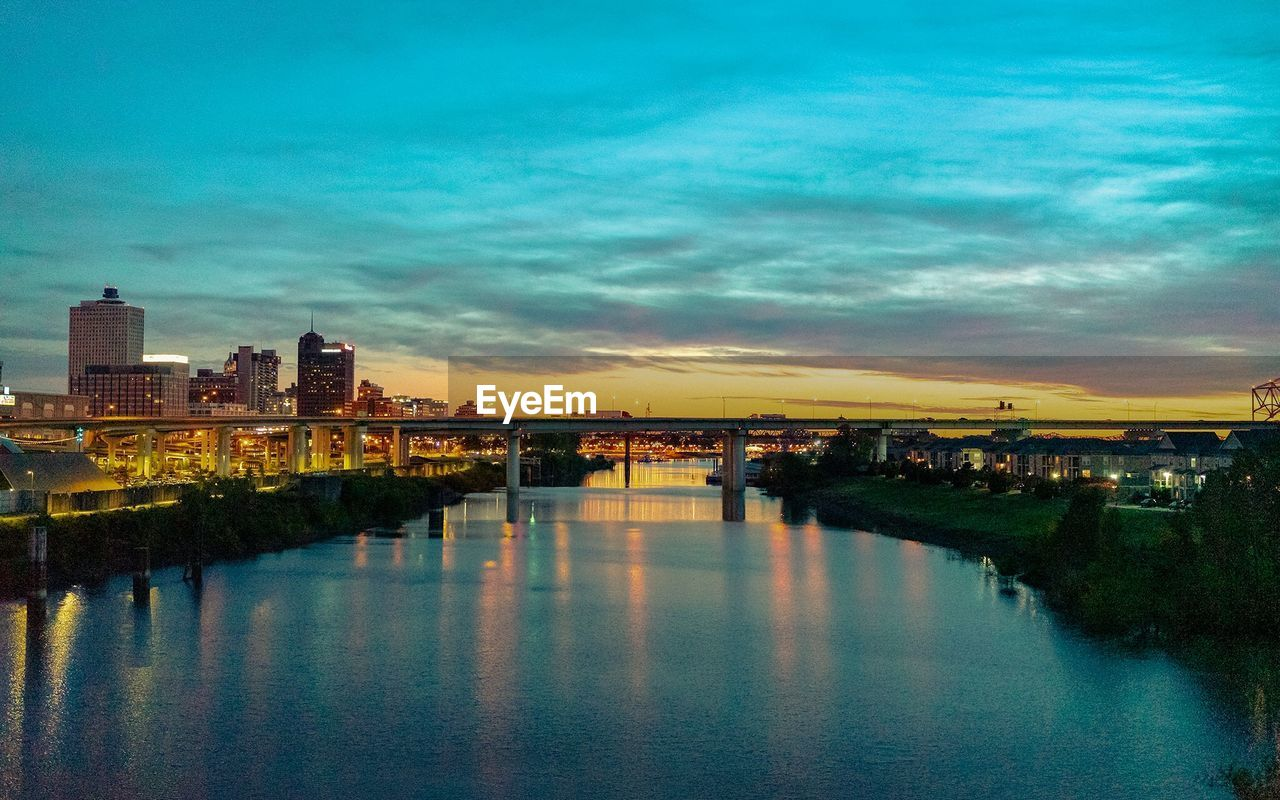 Scenic View Of River By Illuminated Buildings Against Sky At Sunset