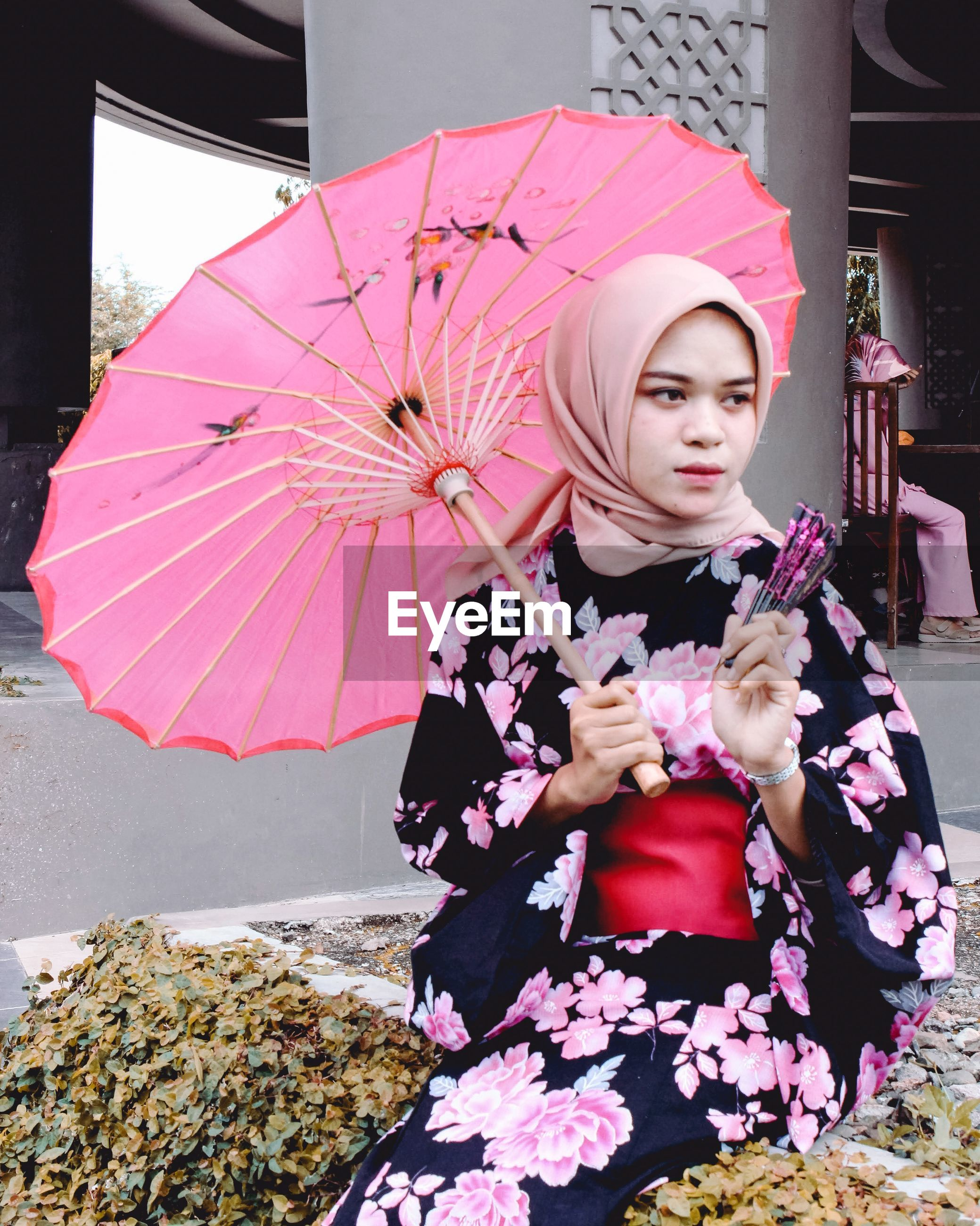 Woman holding pink umbrella and hand fan while sitting outdoors