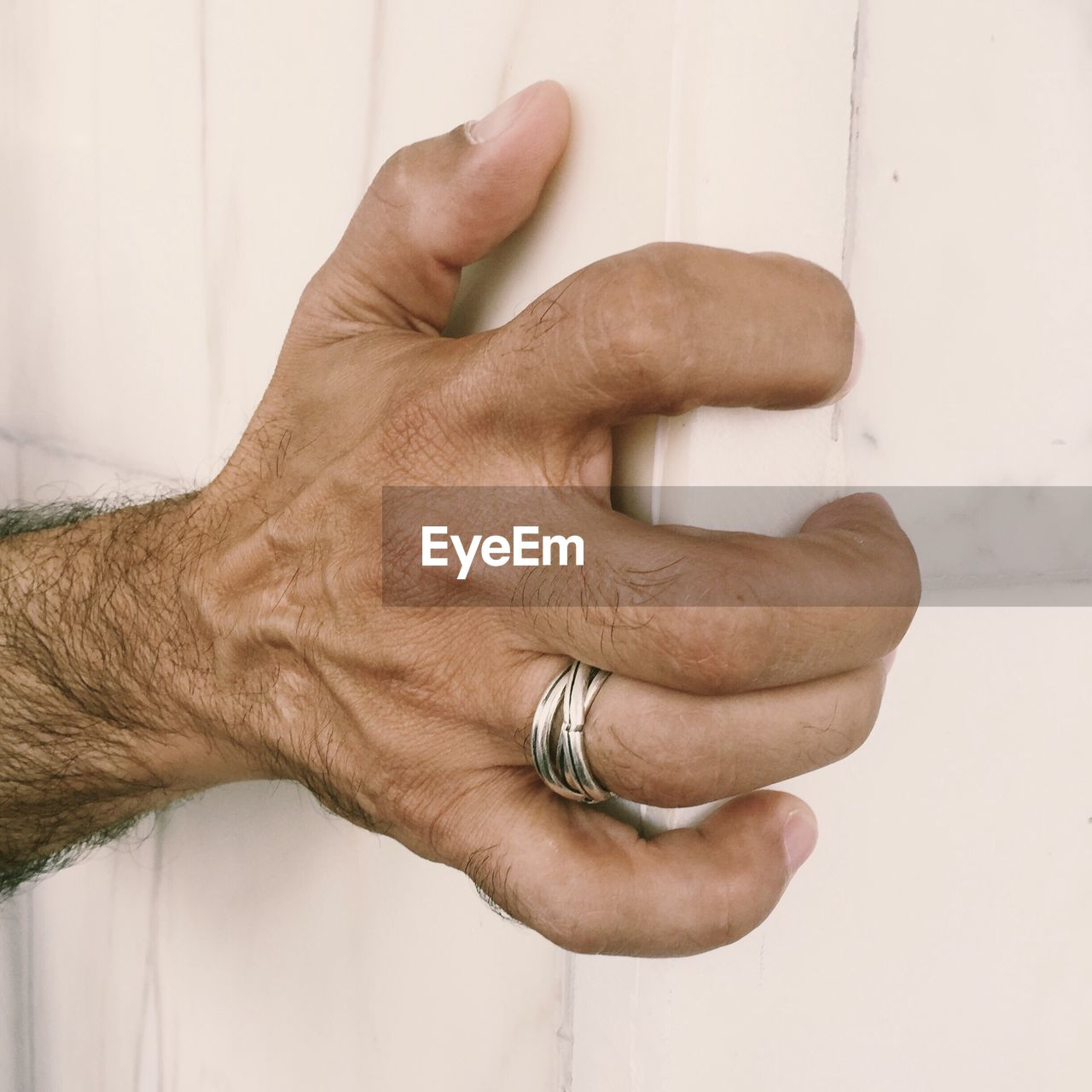 Cropped Hand Of Man Holding Wooden Cabinet At Home
