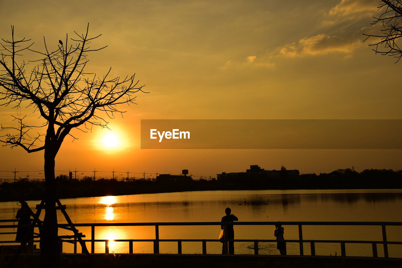 sunset, sky, silhouette, beauty in nature, orange color, water, scenics - nature, real people, tree, nature, cloud - sky, lake, reflection, railing, standing, outdoors, idyllic, tranquility, bare tree