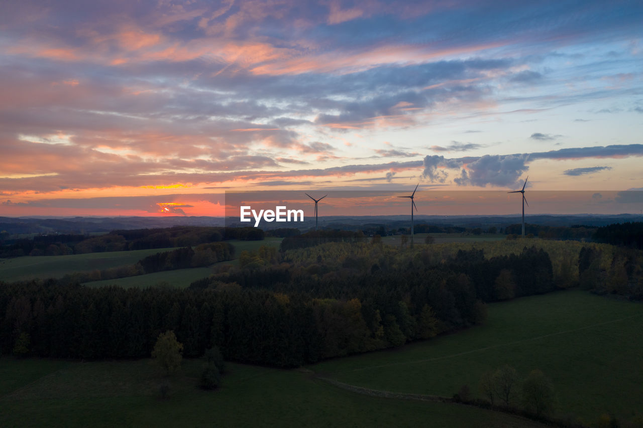 sky, environment, sunset, cloud - sky, renewable energy, fuel and power generation, wind turbine, turbine, environmental conservation, alternative energy, beauty in nature, landscape, scenics - nature, wind power, tranquil scene, tranquility, nature, land, field, tree, no people, outdoors, sustainable resources, power supply