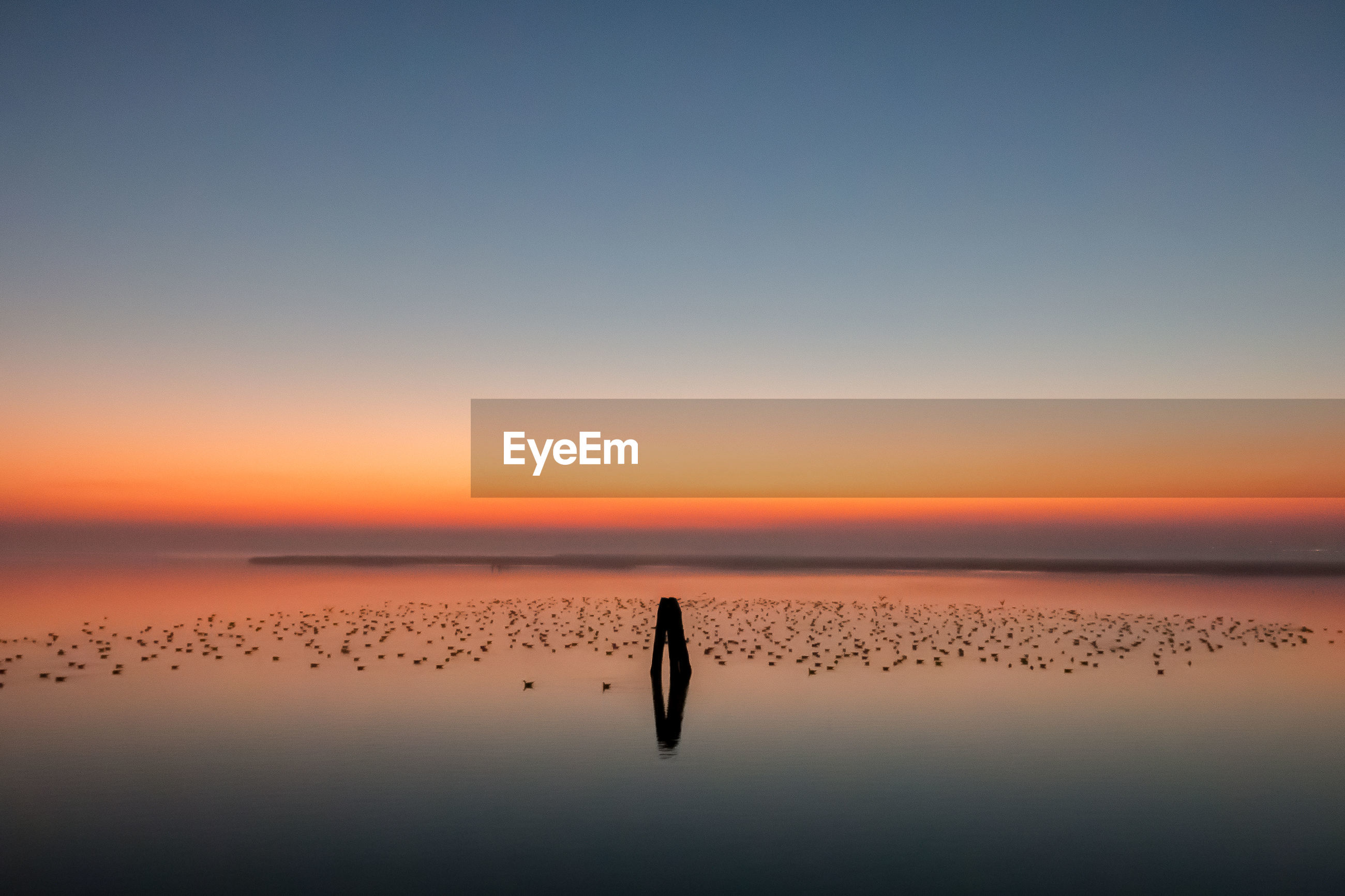 Scenic view of lagoon against sky during sunrise
