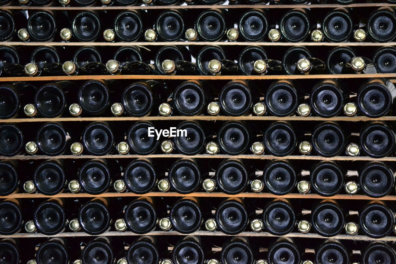 in a row, large group of objects, wine bottle, wine cellar, bottle, alcohol, drink, indoors, cellar, wine, full frame, food and drink, refreshment, container, shelf, winery, abundance, no people, order, repetition, winemaking