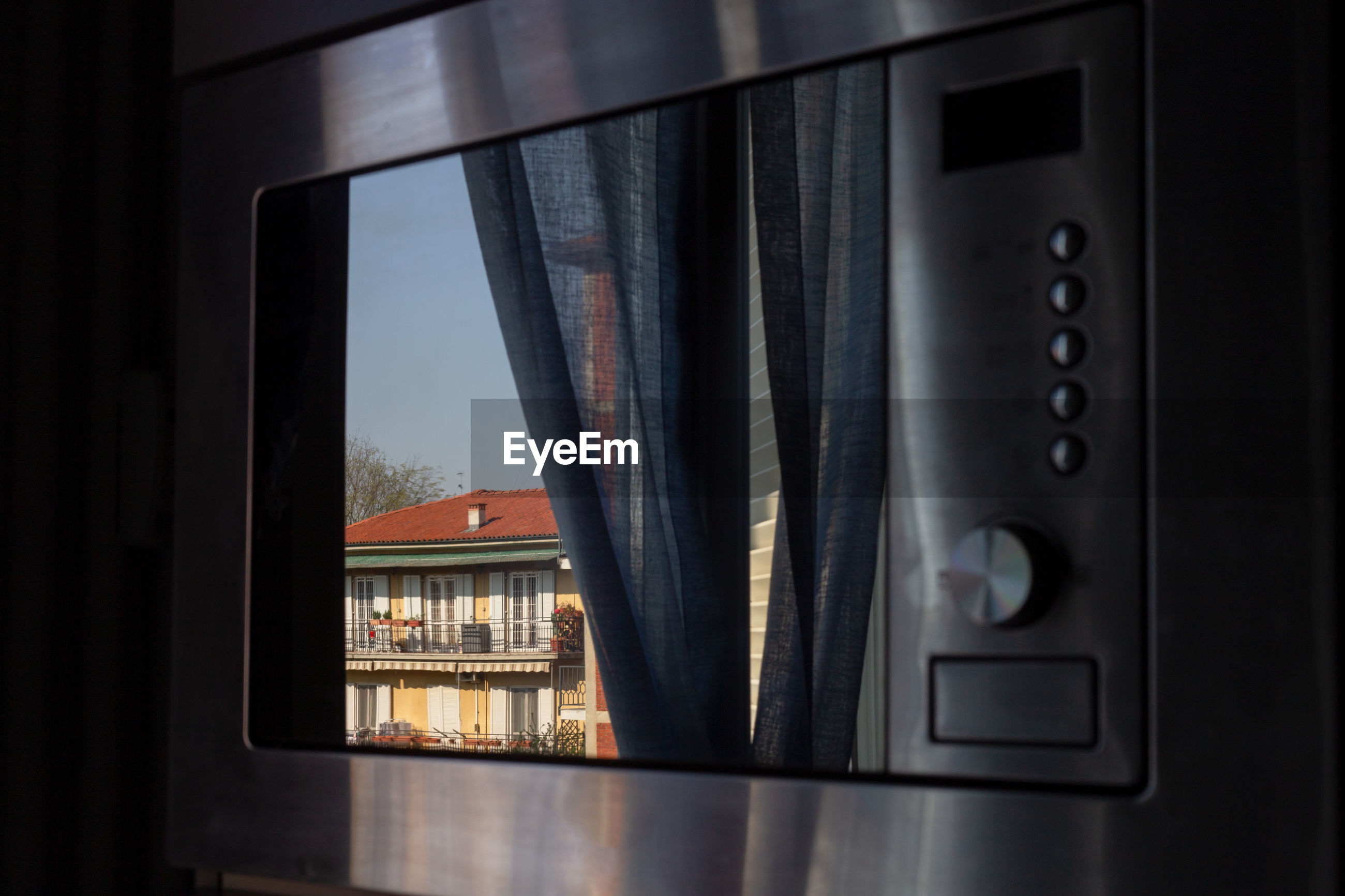 Close-up of oven door and the building reflected