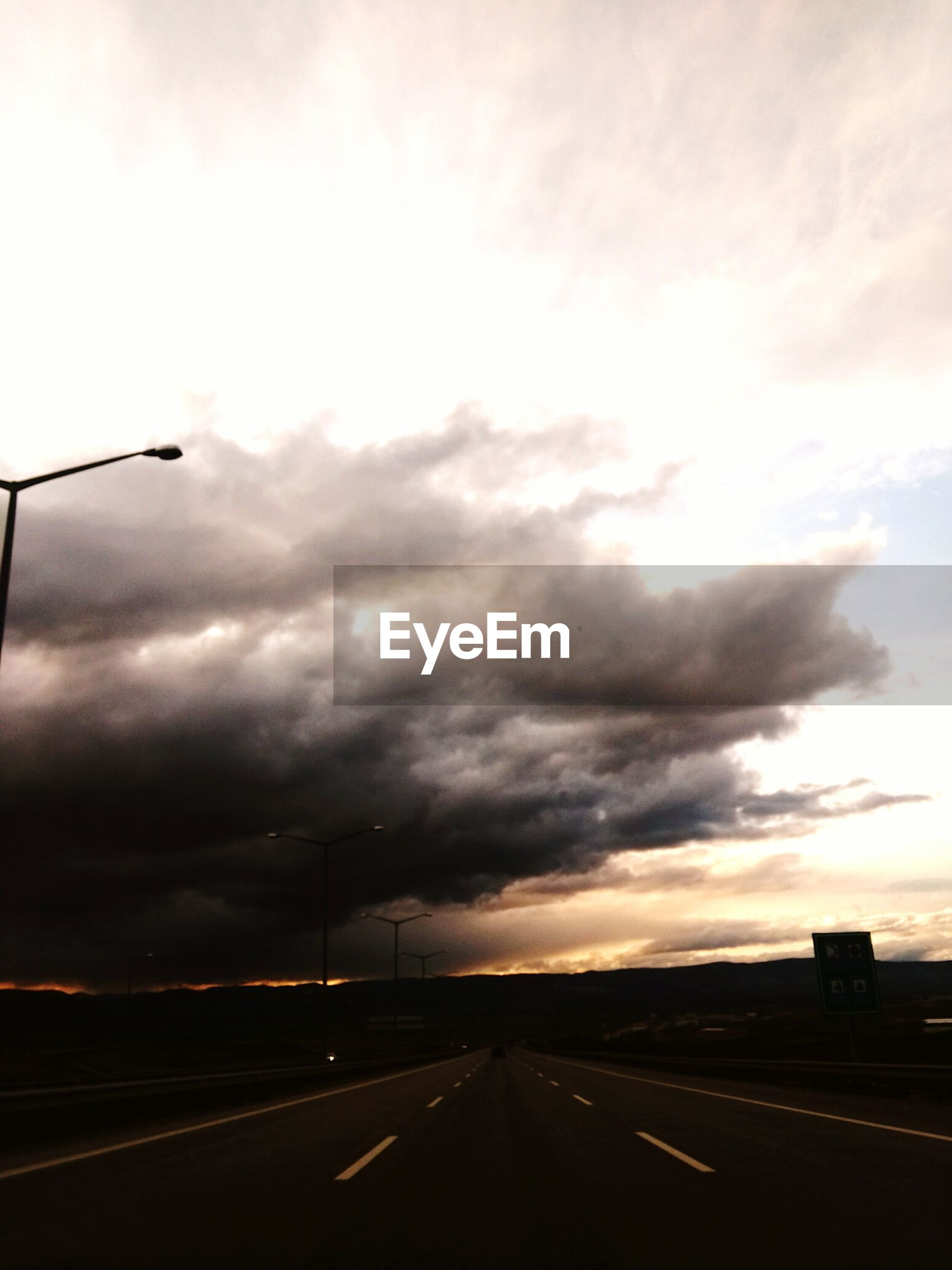 sky, cloud - sky, the way forward, road, cloudy, transportation, road marking, diminishing perspective, overcast, weather, vanishing point, street, cloud, sunset, built structure, building exterior, architecture, storm cloud, street light, dramatic sky
