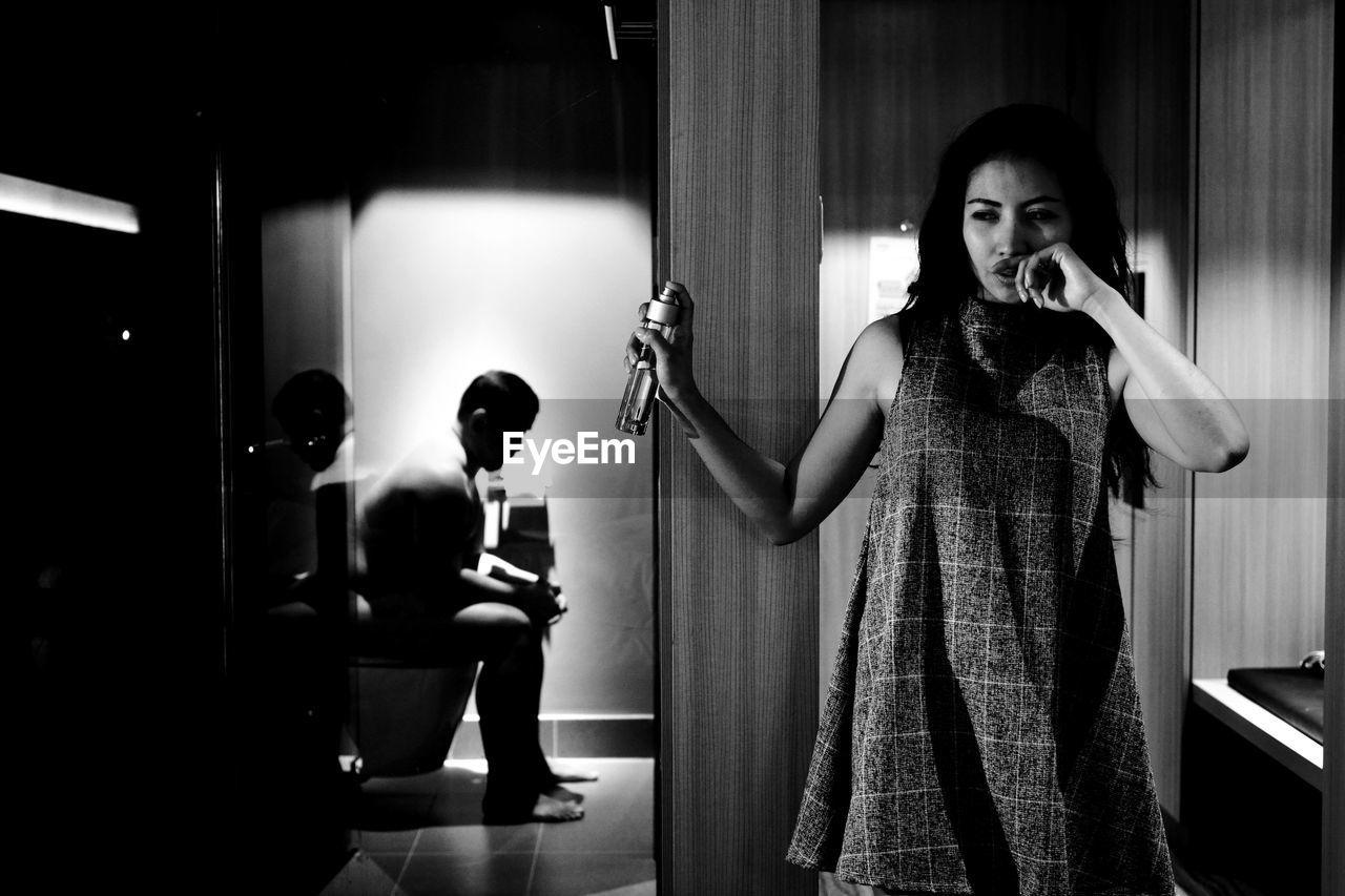 Upset Woman Spraying Air Freshener While Man Sitting In Toilet At Home