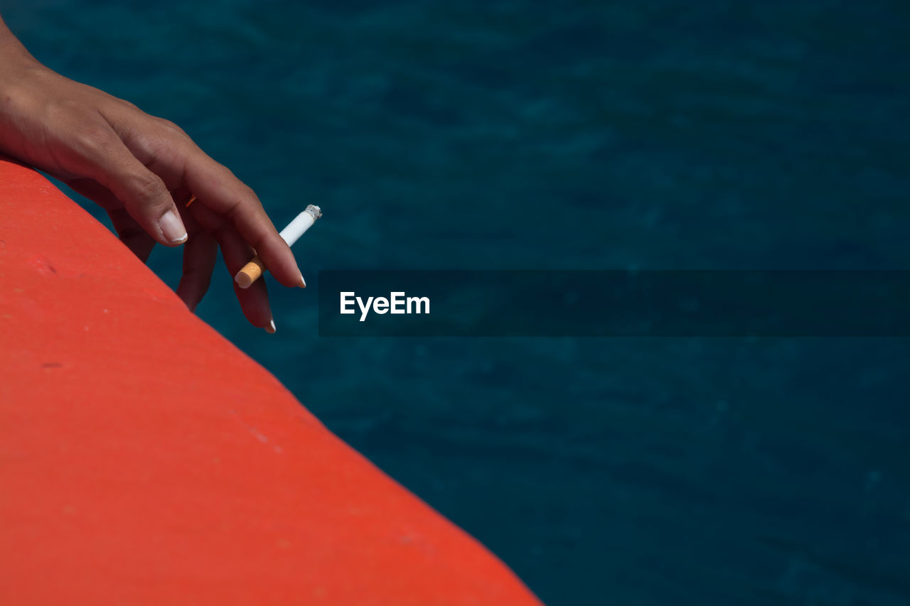 Cropped hand of woman holding cigarette against sea