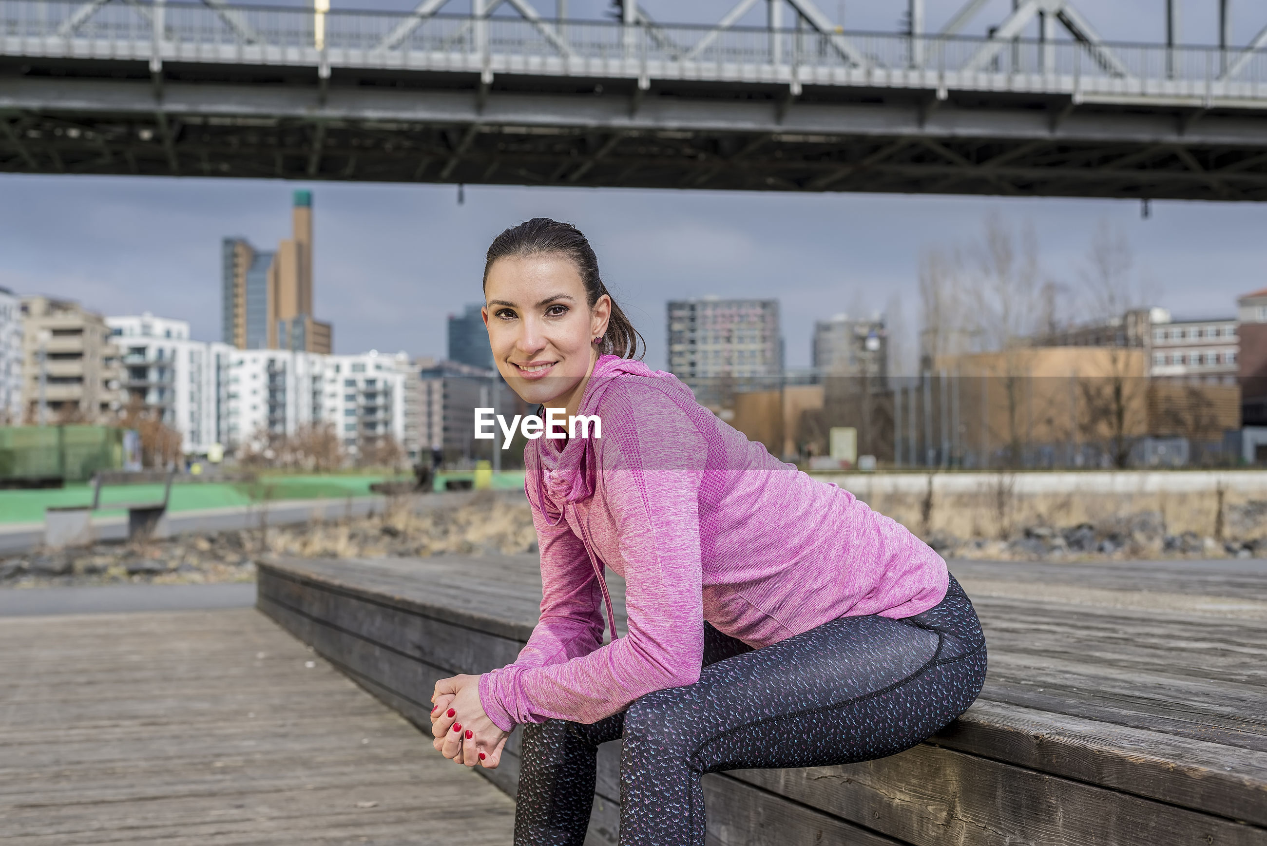 Portrait of smiling woman exercising in city