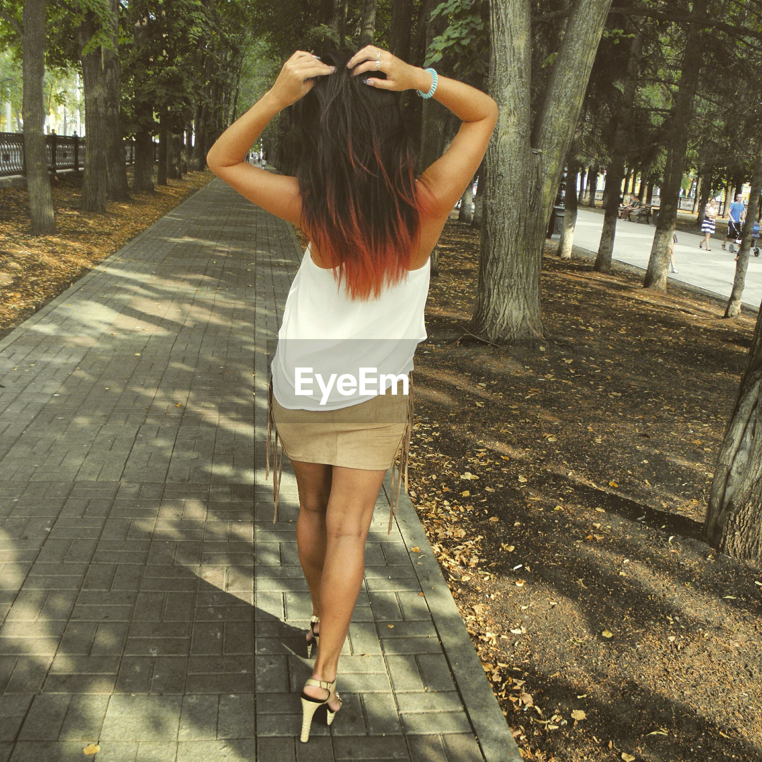 Rear view of young woman standing on footpath against tree