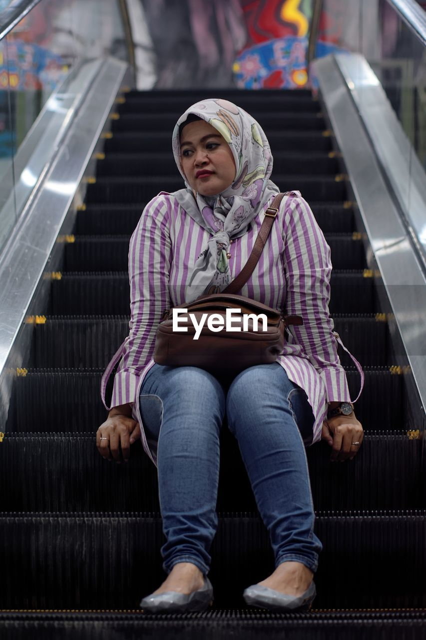 Thoughtful mid adult woman wearing hijab while sitting on escalator