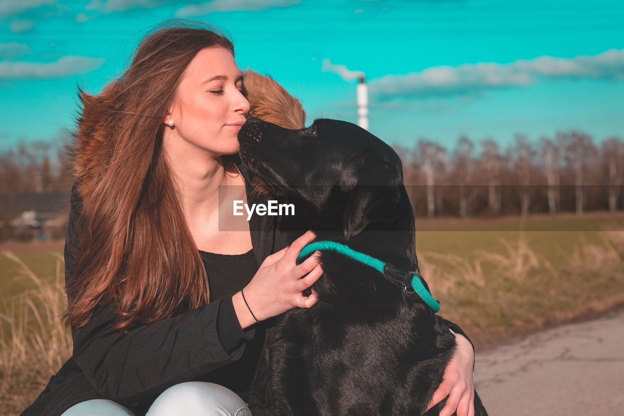 Young Woman Kissing Dog At Public Park