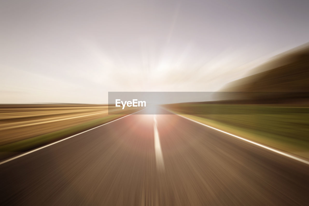 sky, blurred motion, road, sunlight, transportation, no people, nature, speed, motion, the way forward, landscape, sunbeam, direction, day, sun, outdoors, lens flare, symbol, diminishing perspective, vanishing point, dividing line