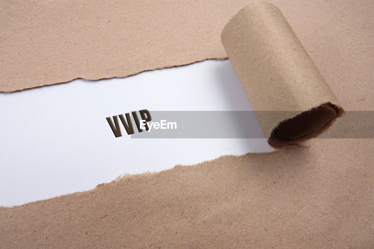 High angle view of torn brown paper with text on white background