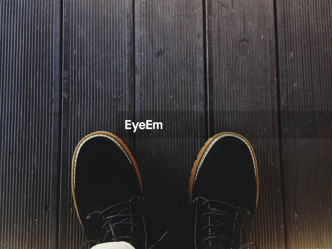 shoe, human leg, low section, standing, body part, one person, human body part, real people, wood - material, personal perspective, high angle view, day, pattern, lifestyles, unrecognizable person, outdoors, directly above, close-up, footpath, brown, human foot