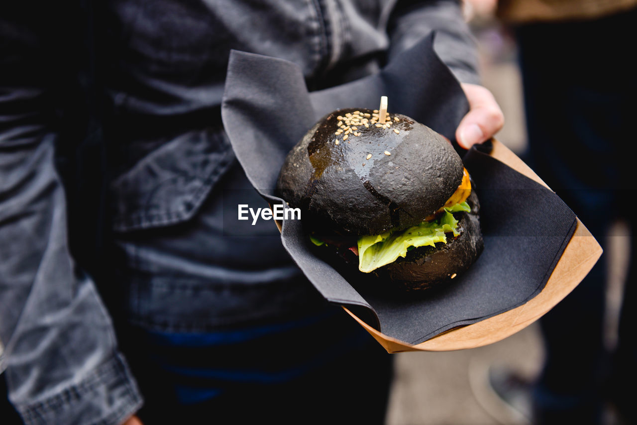 Midsection Of Person Holding Hamburger At Market